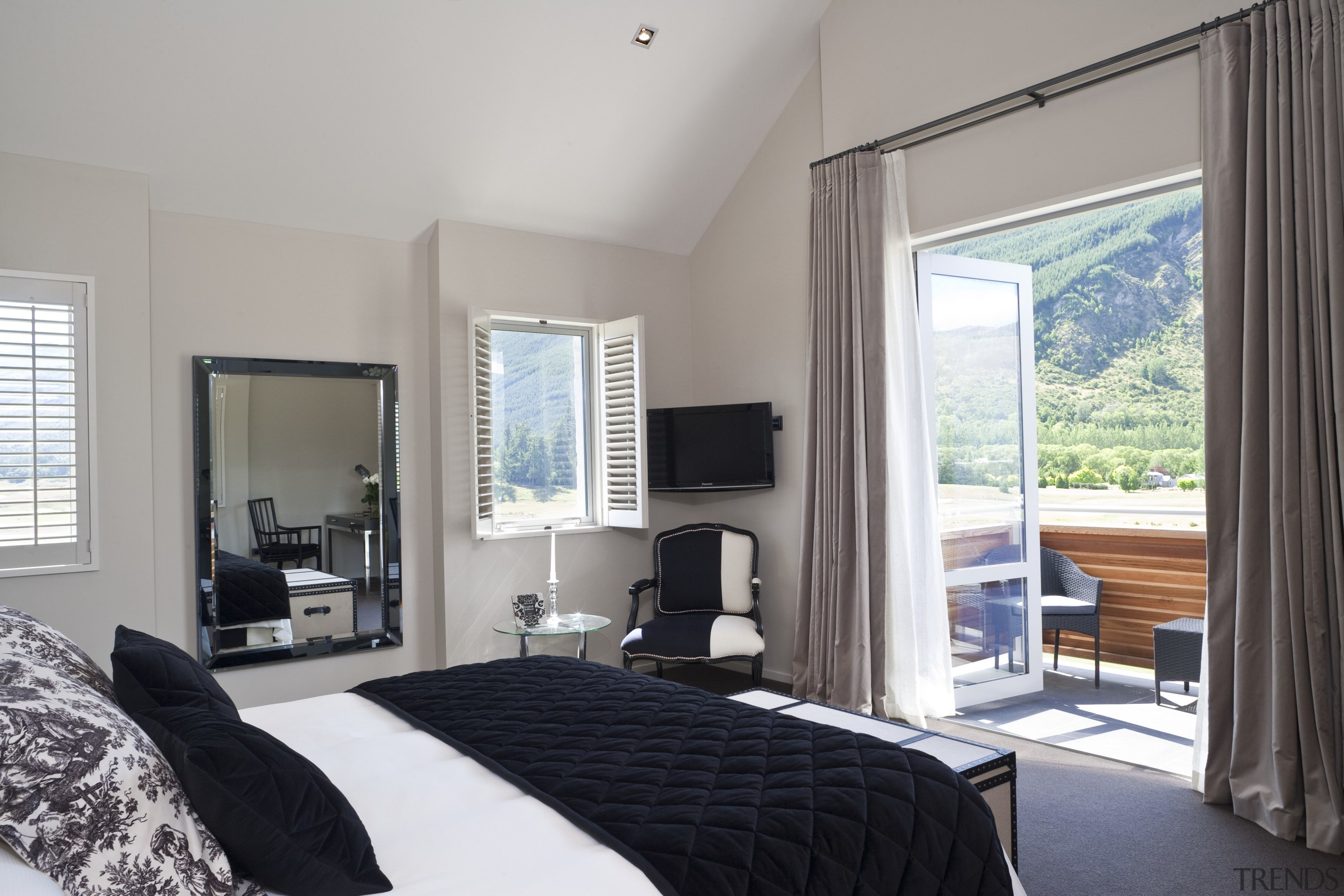 View Of Bedroom Featuring Bed With White Linen, Black Headboard,