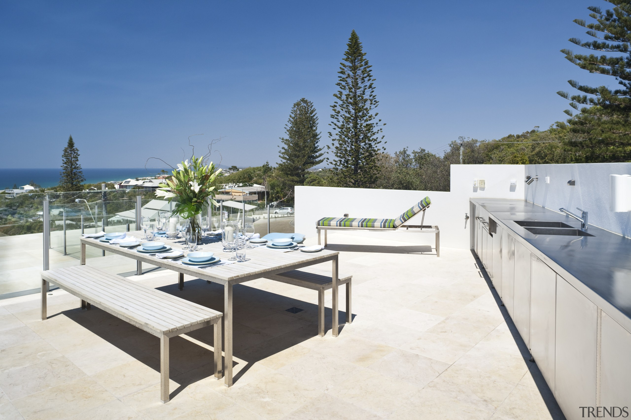 View of rooftop terrace which features paving, outdoor apartment, architecture, estate, furniture, home, house, outdoor furniture, penthouse apartment, property, real estate, sunlounger, table, white, teal