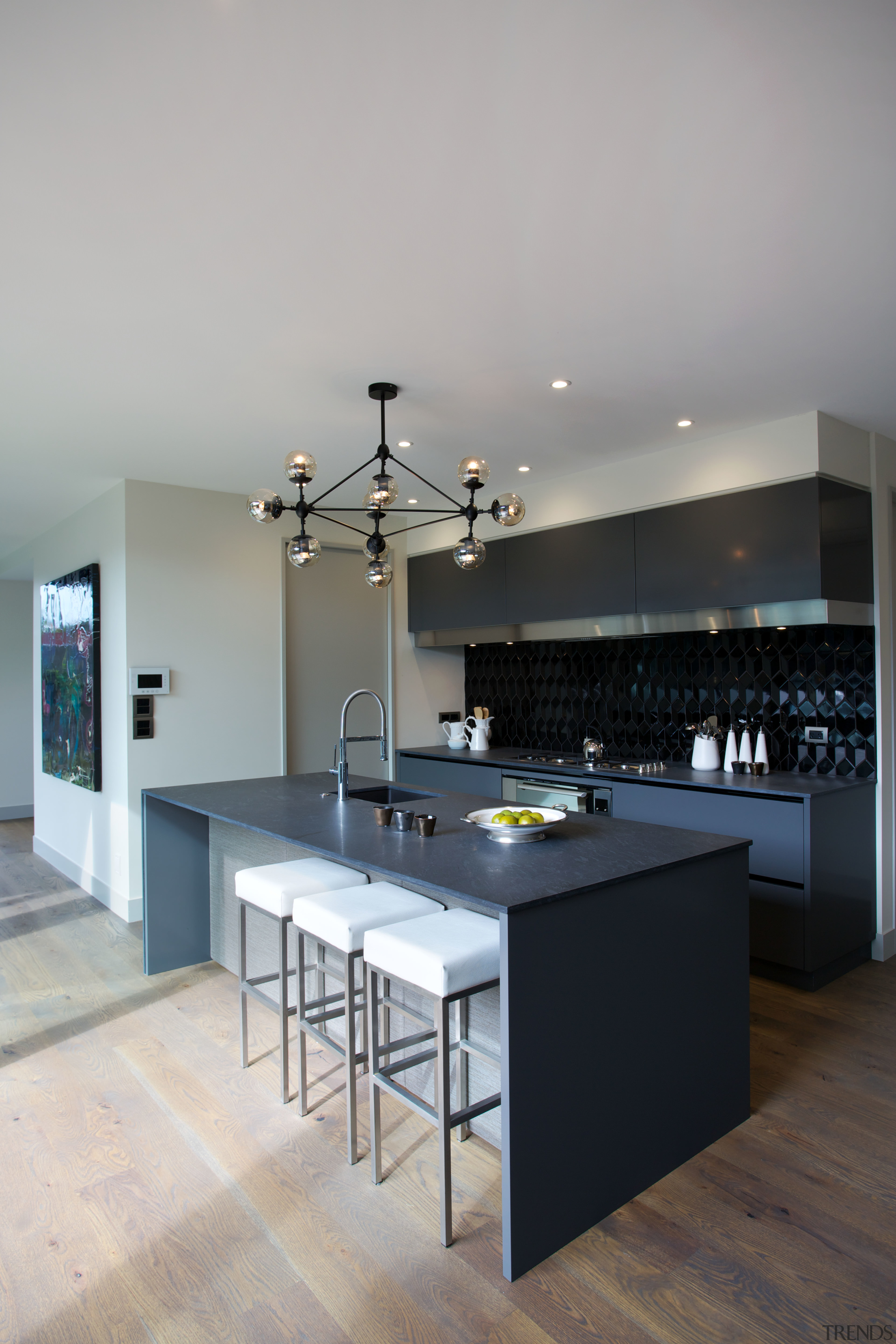 A waterfall countertop and black colour palette give countertop, floor, interior design, kitchen, table, gray