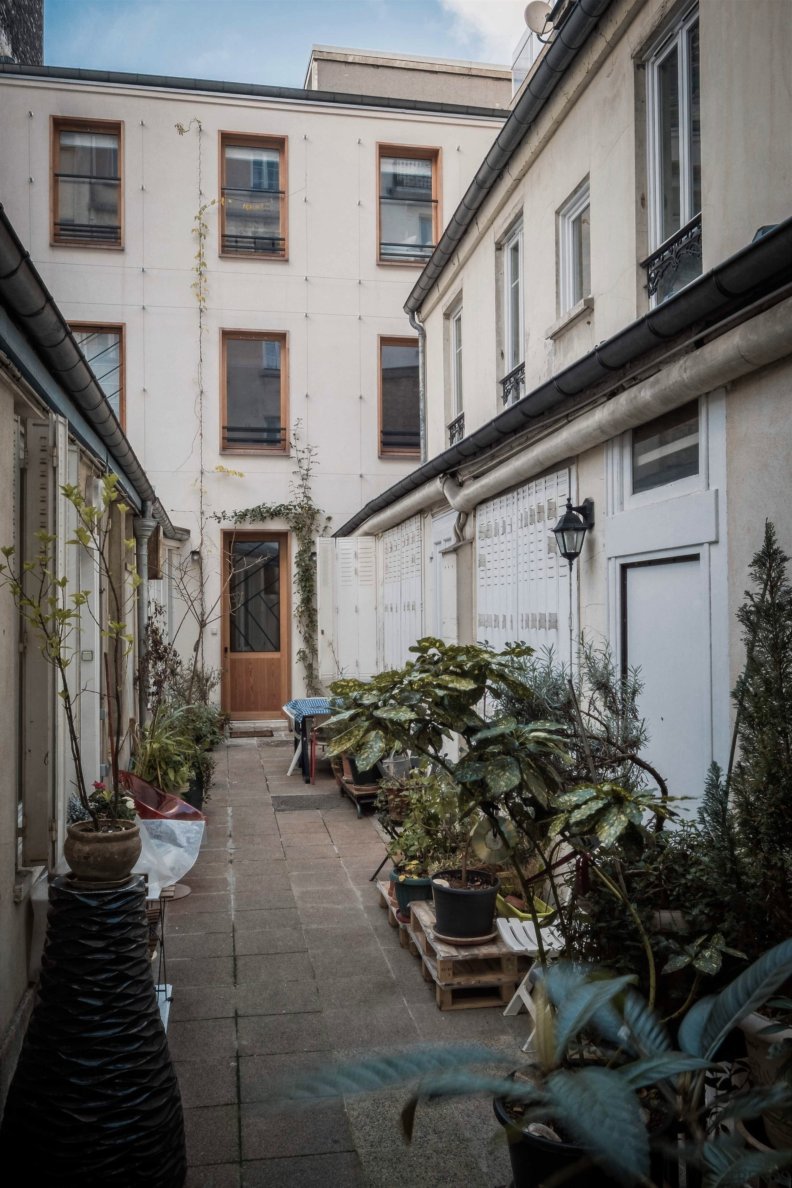 A 3 storey family home in Paris gets alley, architecture, building, courtyard, facade, house, infrastructure, neighbourhood, road, street, town, tree, gray, black