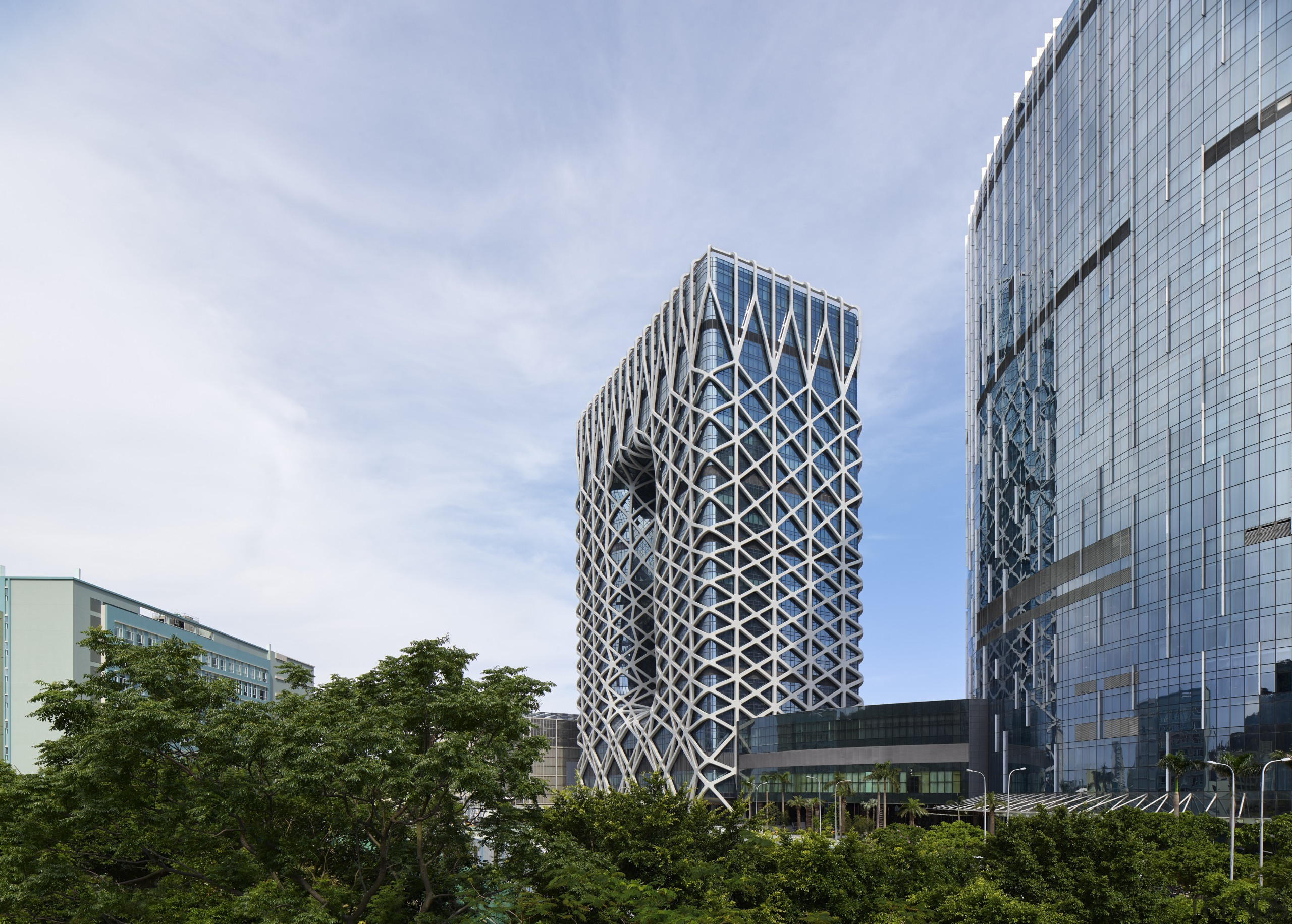 The glazed facade behind Morpheus Hotel's exoskeleton comprises architecture, building, city, condominium, corporate headquarters, daytime, facade, headquarters, metropolis, metropolitan area, mixed use, residential area, sky, skyscraper, tower block, tree, urban area, white