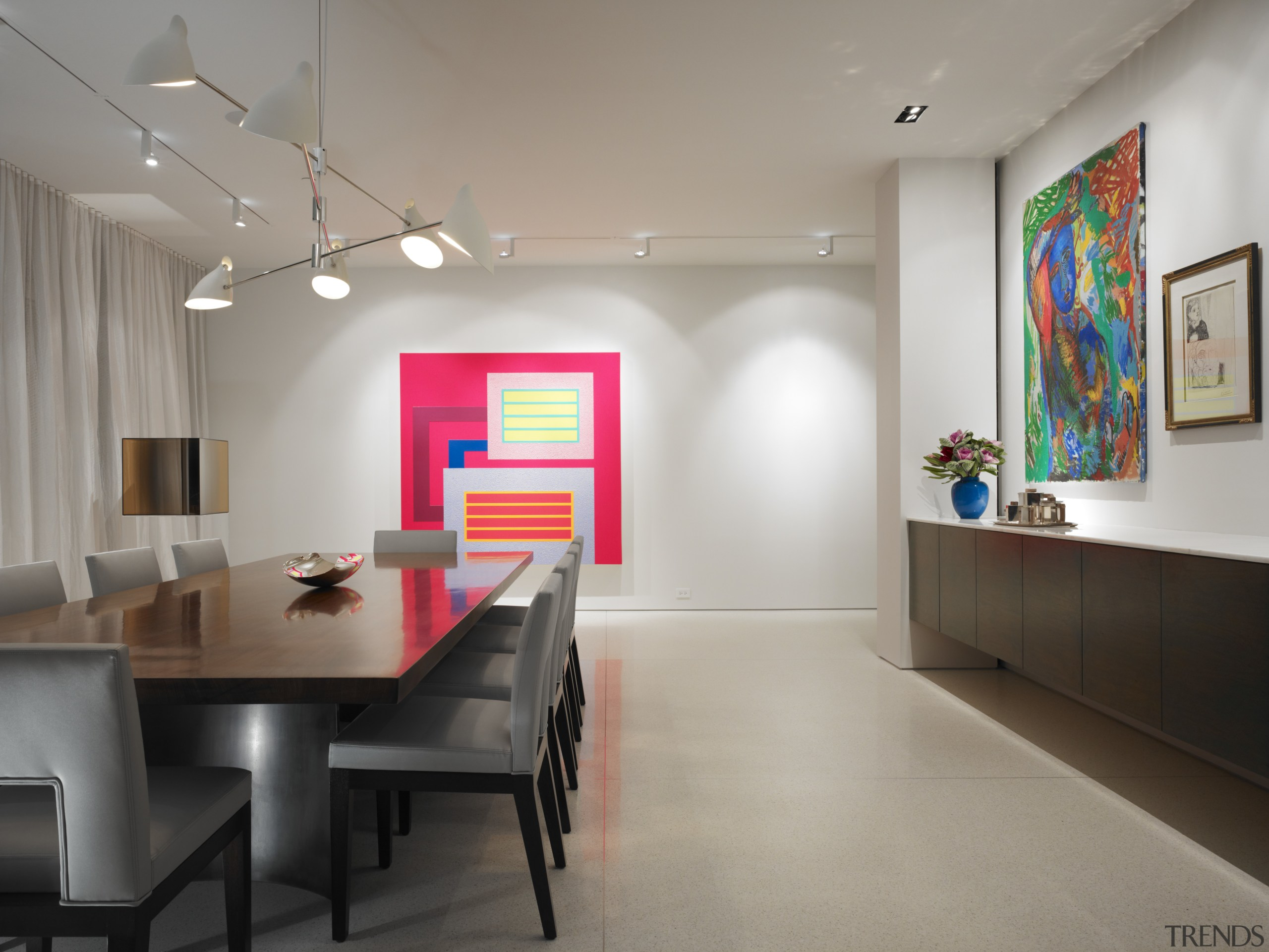 In this spacious dining area, the painting on architecture, ceiling, dining room, interior design, room, table, wall, gray