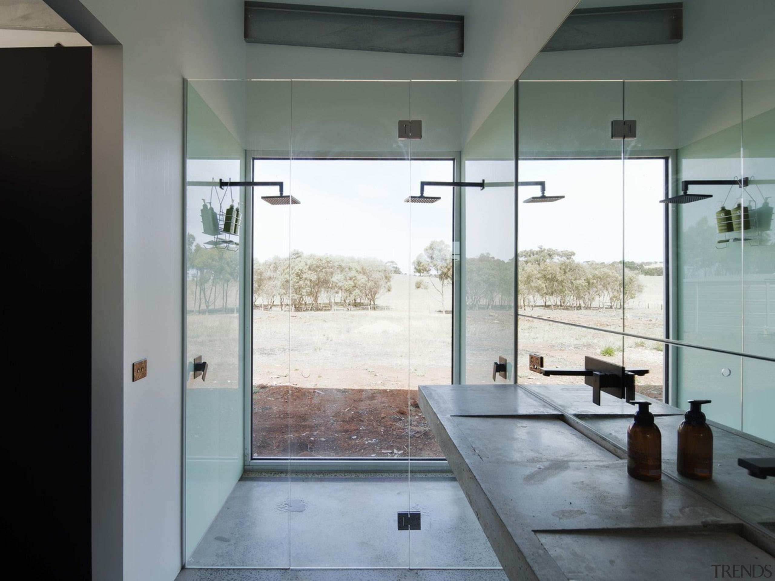 The double shower lacks privacy, but makes up architecture, bathroom, door, floor, flooring, glass, house, interior design, plumbing fixture, room, tile, gray