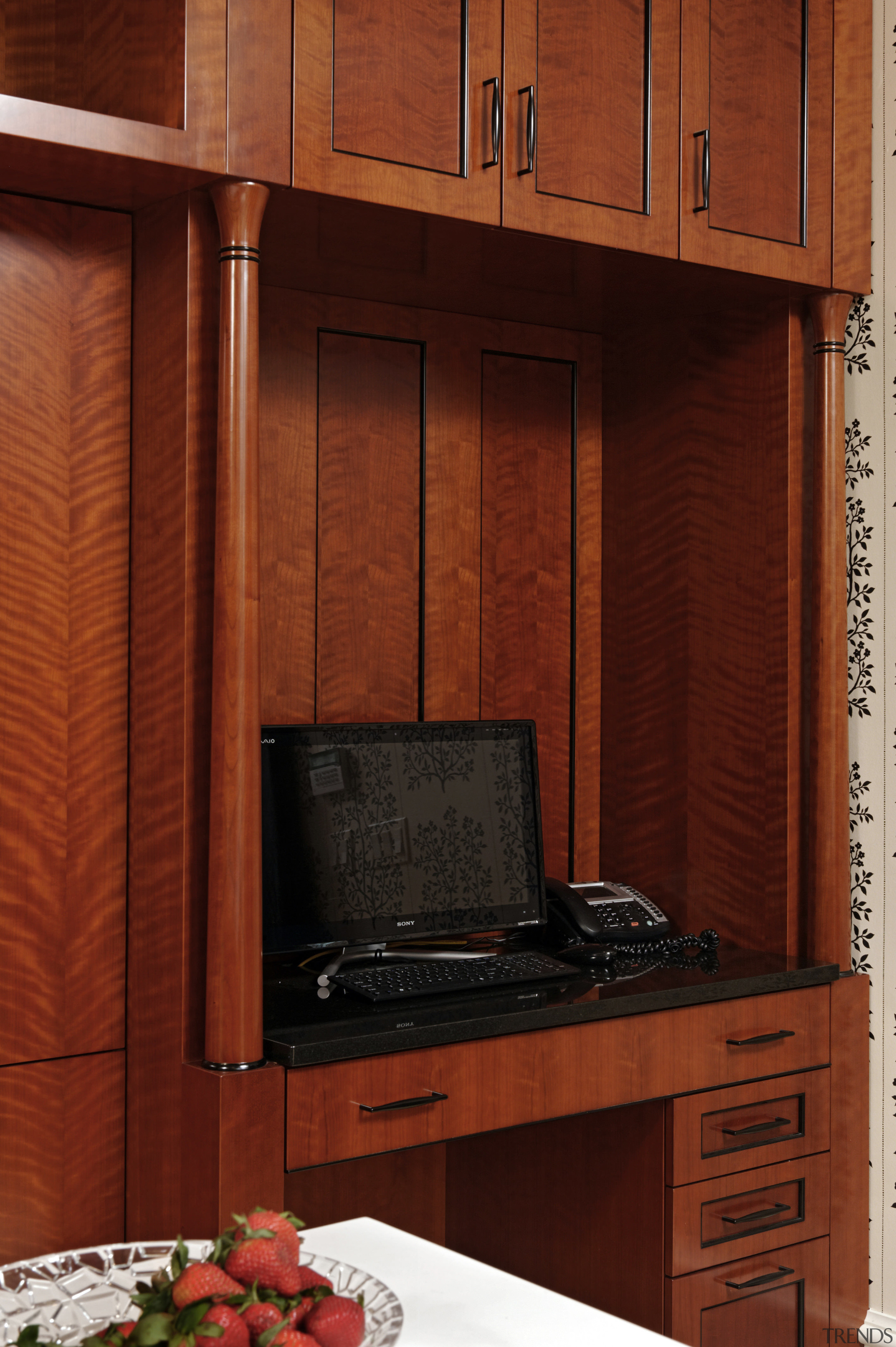 A small writing area cum home office tucked cabinetry, furniture, wall, wood, wood stain, red