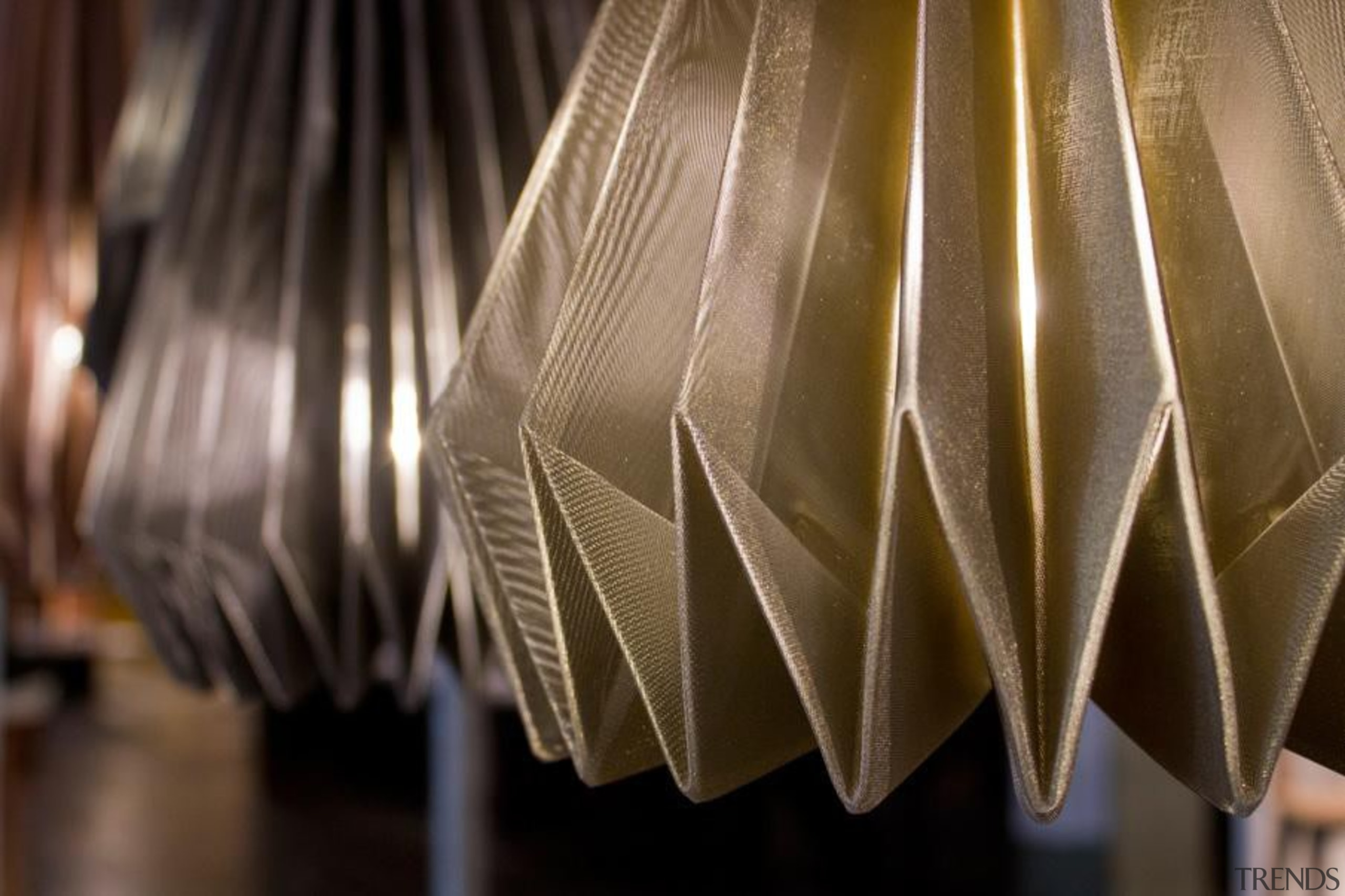 A range of folded metallic fabrics  are interior design, lampshade, light, light fixture, lighting, lighting accessory, material, brown, black
