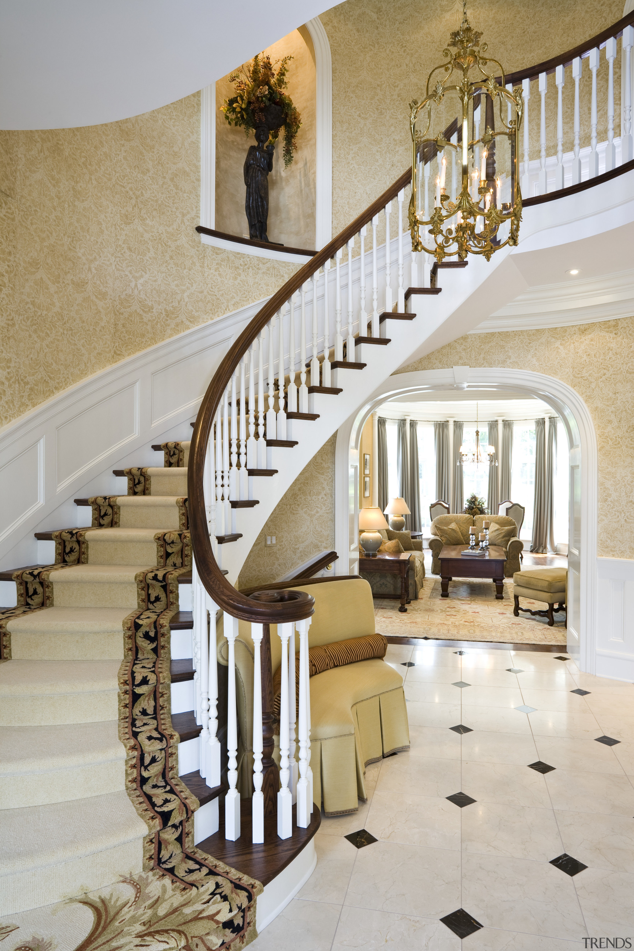 View Of A Sweeping Staircase With Dark Stained Timber Handrail And