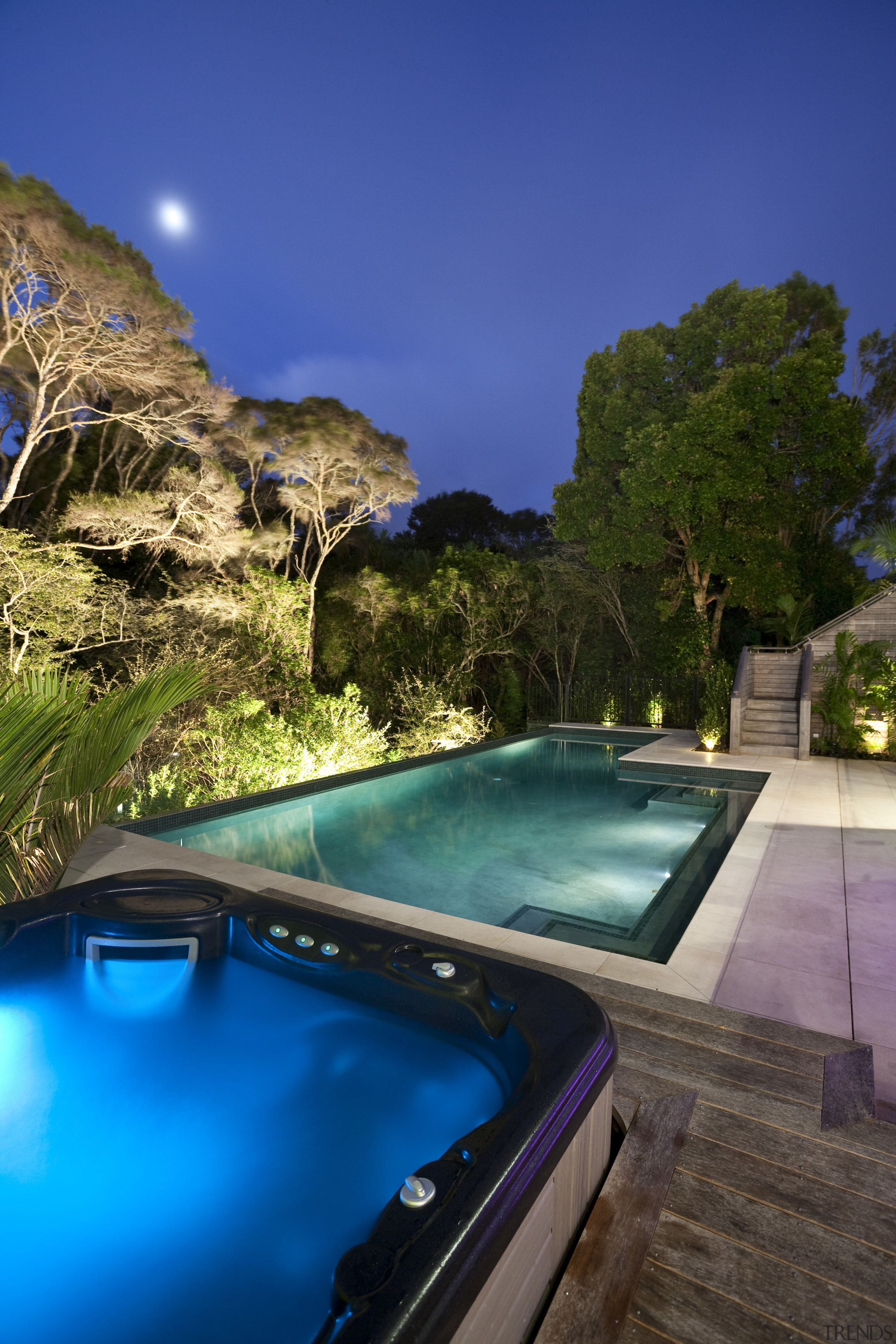 View of sleek poolscape with textured stone wall, estate, leisure, lighting, real estate, reflection, resort, sky, swimming pool, tree, water, blue