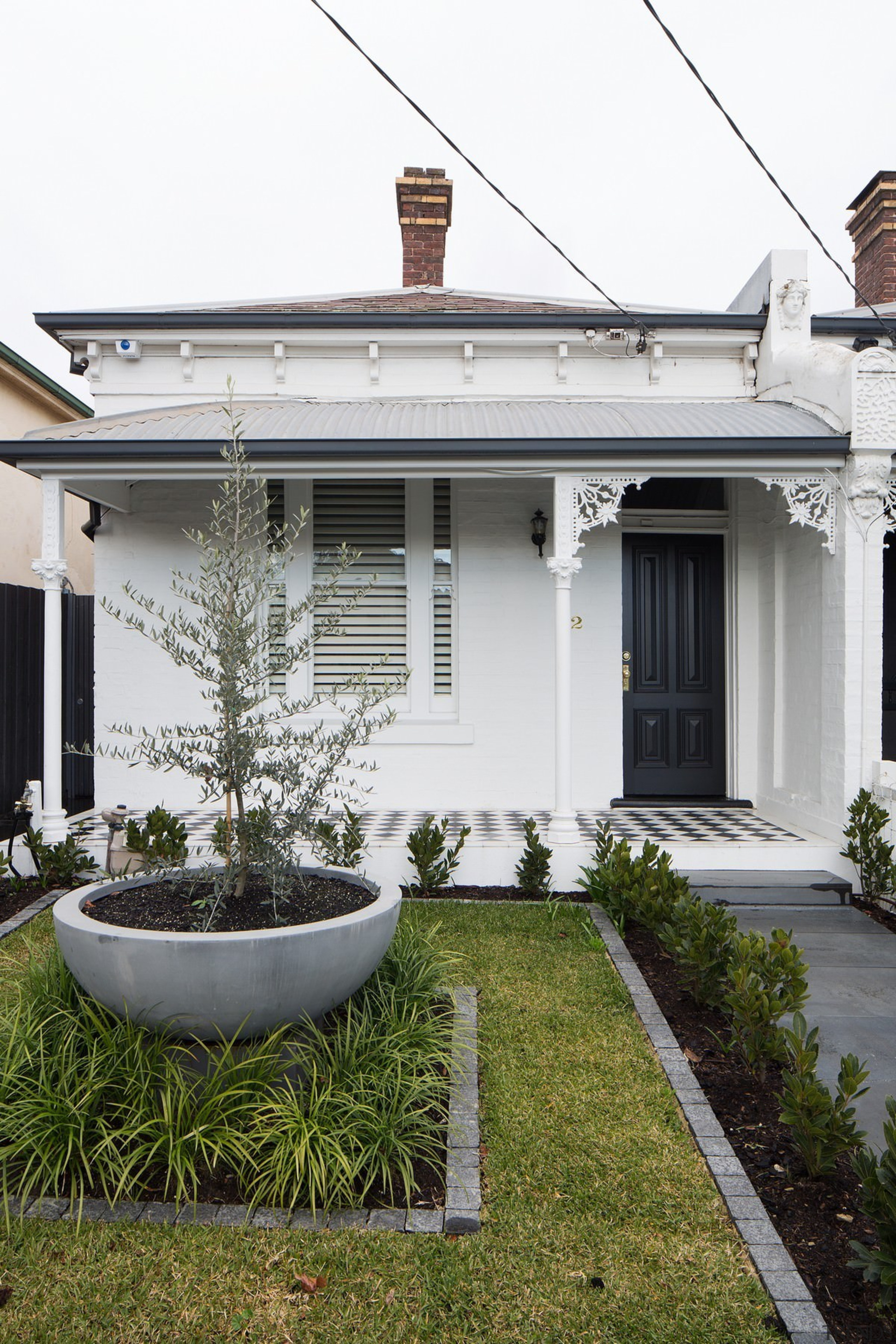From the street, only subtle changes hint at architecture, backyard, facade, home, house, outdoor structure, property, real estate, residential area, window, yard, white