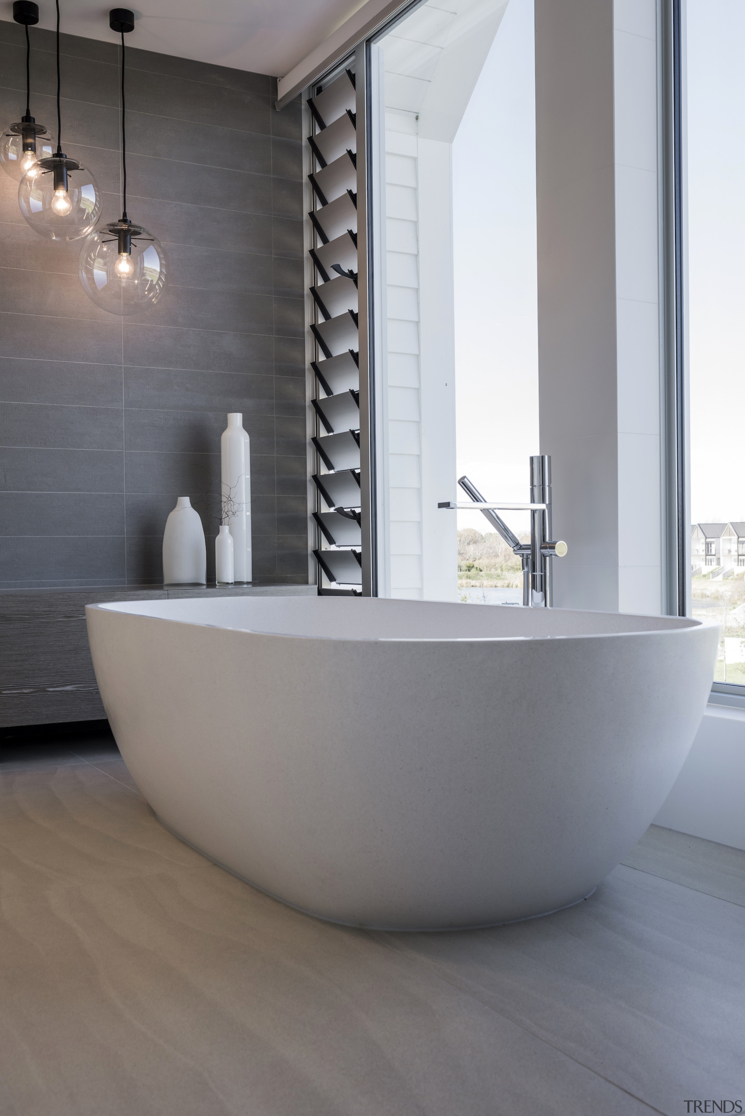 The curvaceous free-standing tub is the centrepiece of bathroom, ceramic, floor, flooring, interior design, plumbing fixture, tap, tile, gray, white
