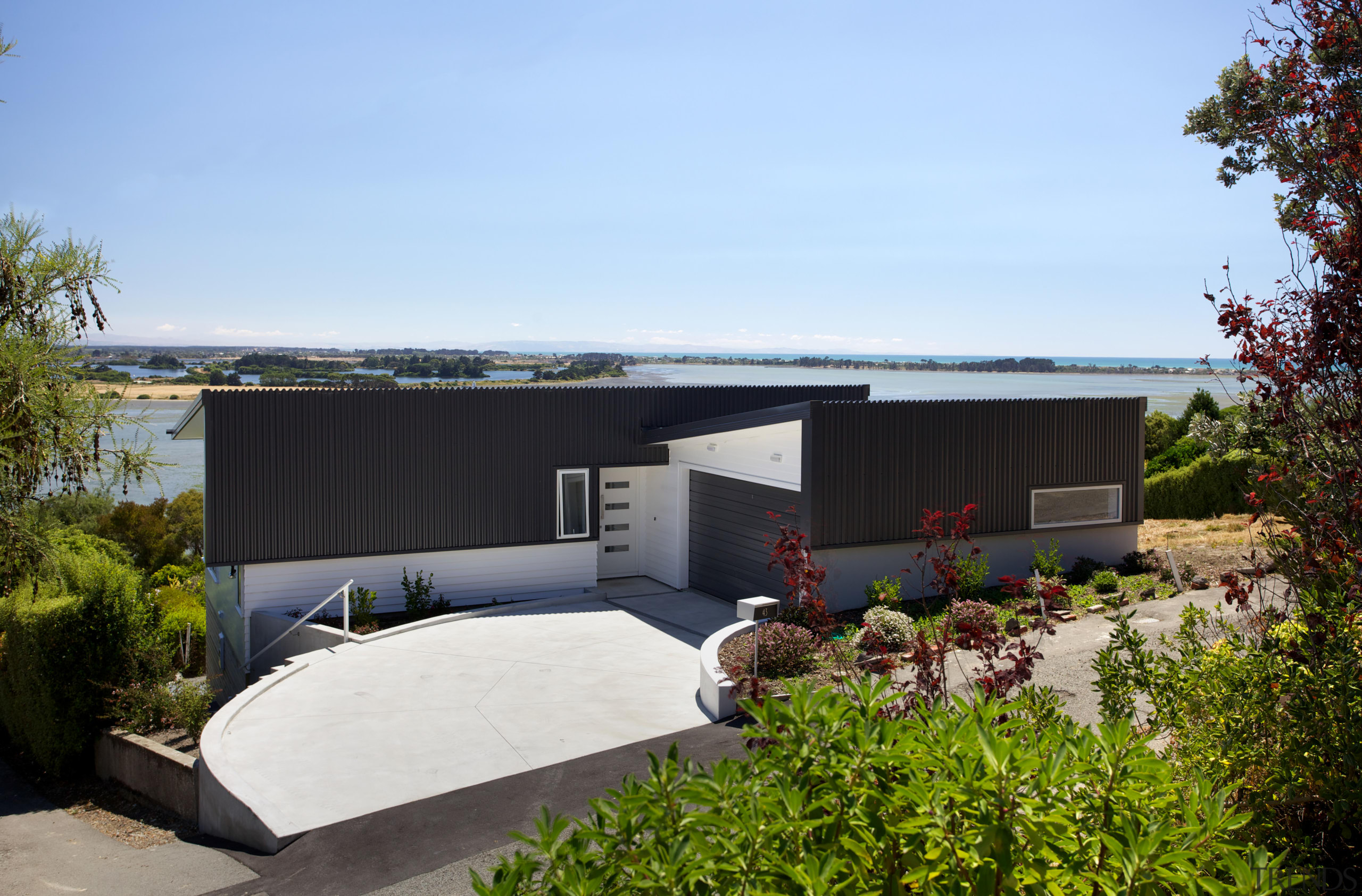 The sloping roof form of this new Christchurch architecture, backyard, cottage, home, house, property, real estate, roof, shed, yard, teal