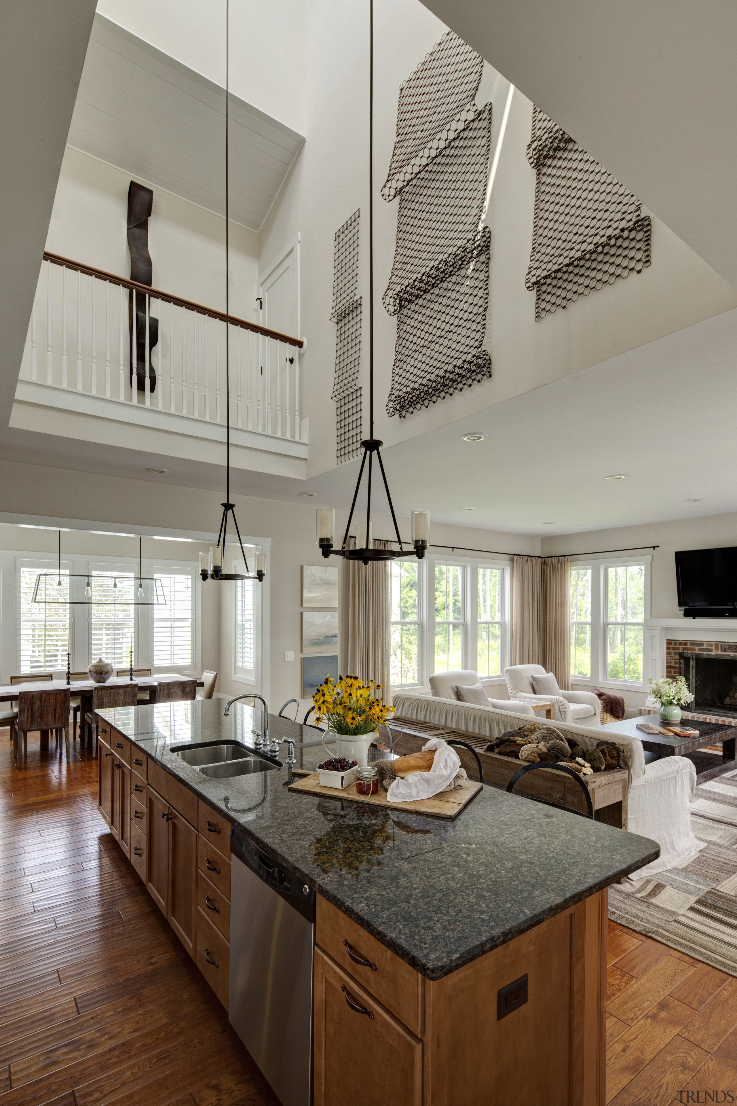 This granite-topped kitchen island, in a double-height open-plan ceiling, countertop, cuisine classique, home, interior design, kitchen, living room, gray, brown