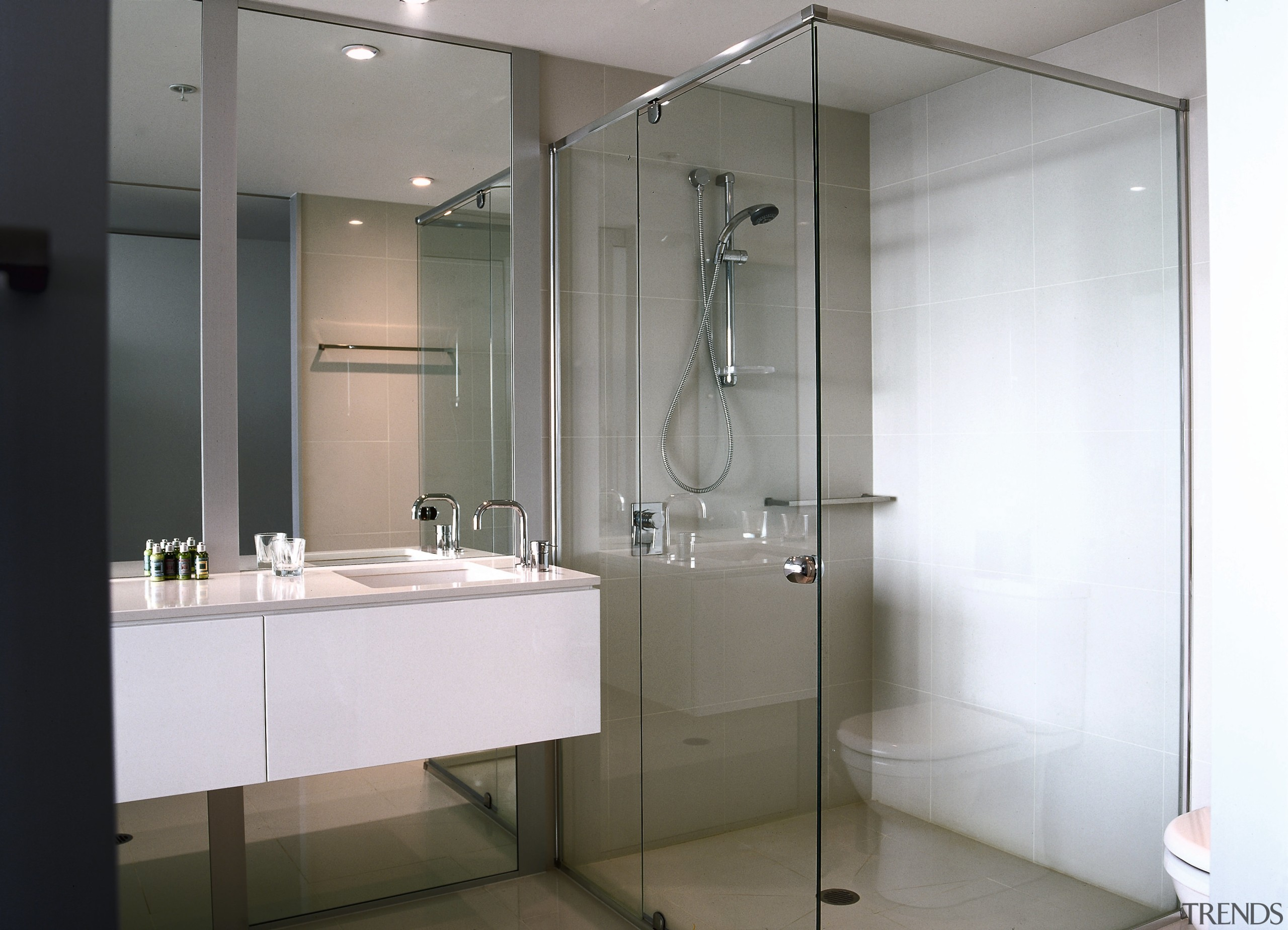 Bathroom with clear glass shower enclosure panels with bathroom, glass, interior design, plumbing fixture, product design, room, gray, white