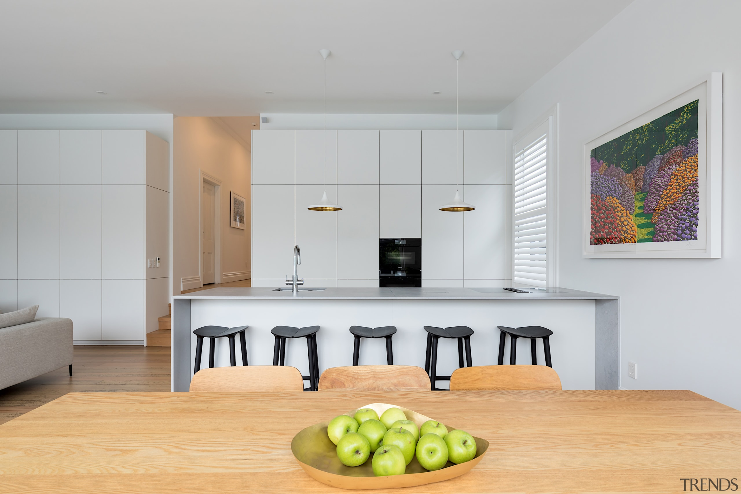 A wall of floor-to-near-ceiling minimalist white cabinetry conceals gray