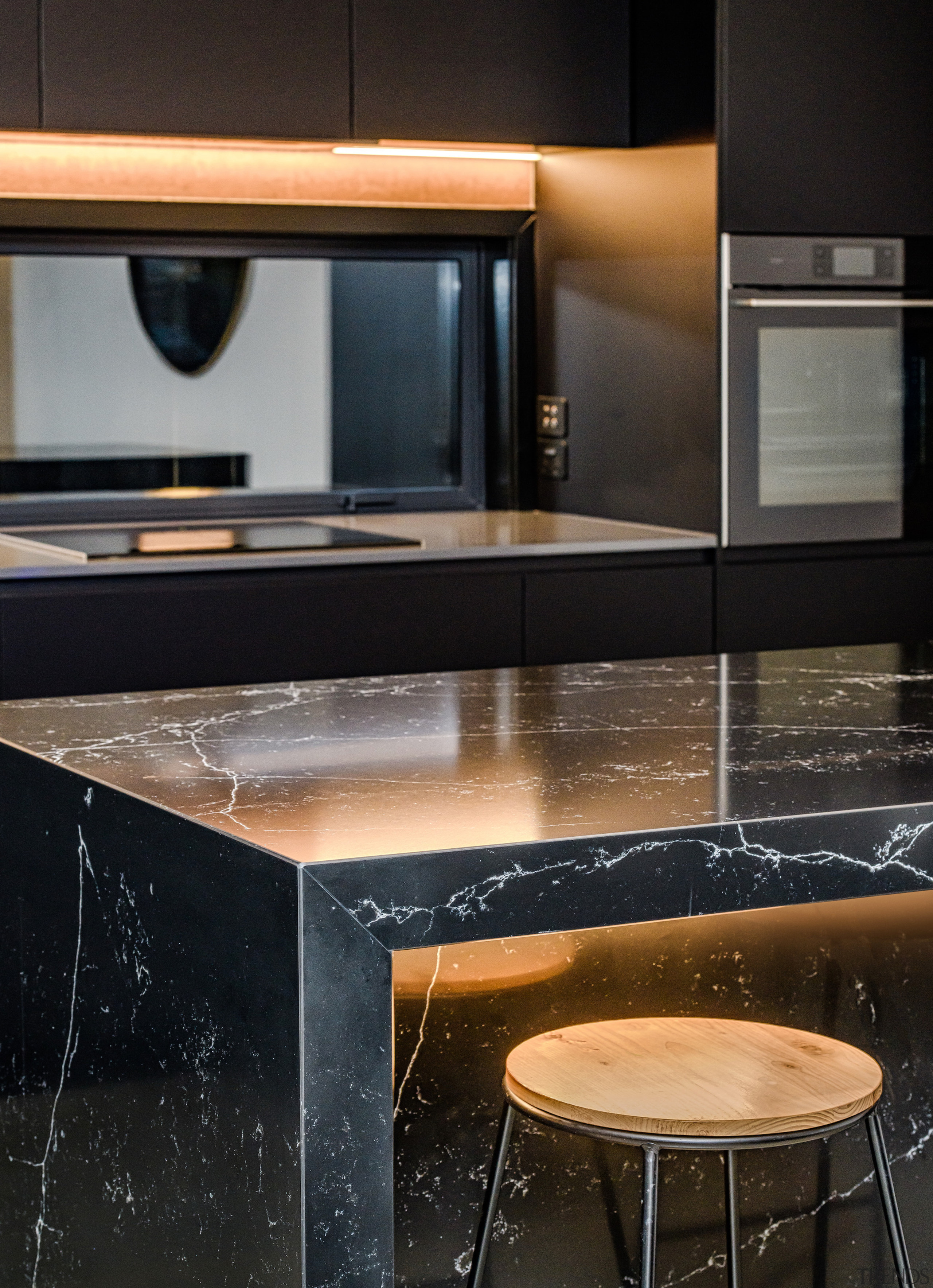 The black stone island is under-lit for dramatic architecture, building, cabinetry, countertop, design, desk, floor, flooring, furniture, glass, granite, home, house, interior design, kitchen, marble, material property, property, room, table, tile, black