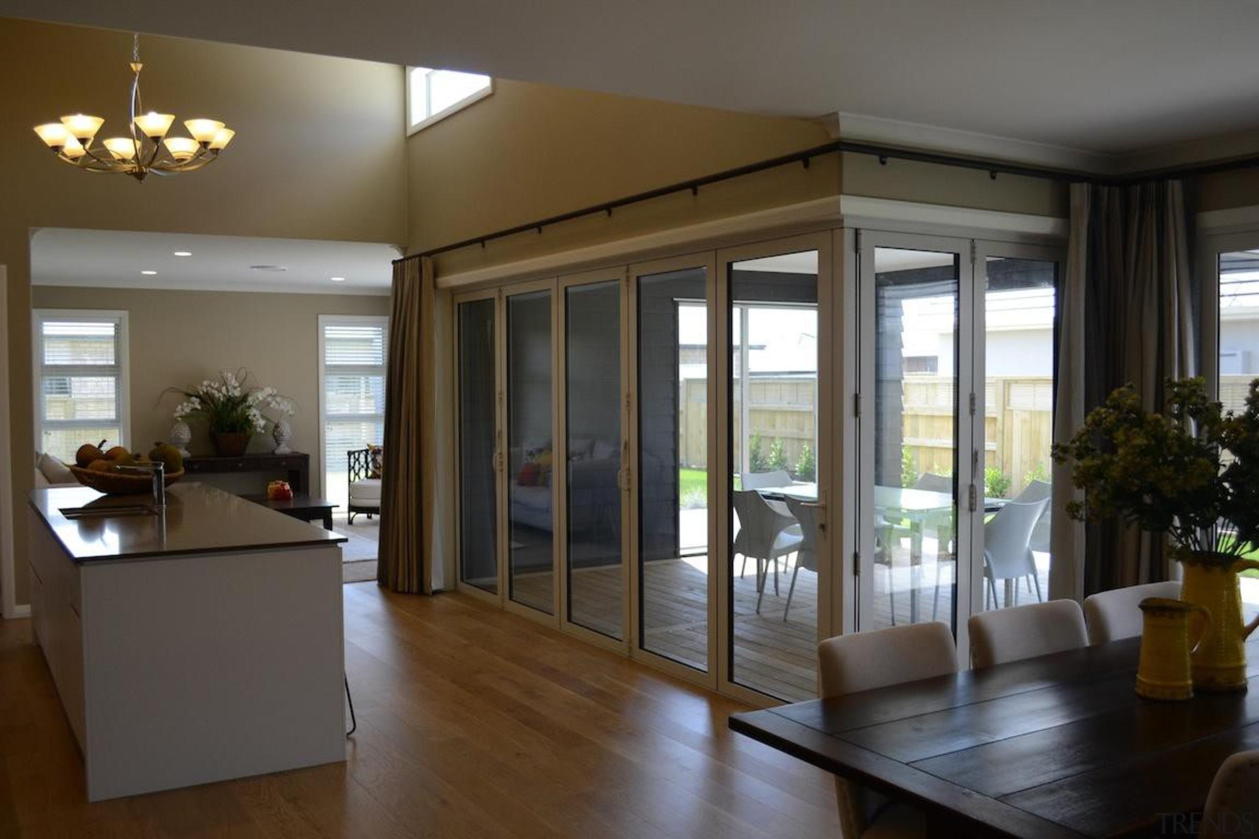 Indoor spaces flow from one side of the door, floor, flooring, house, interior design, property, real estate, window, brown, gray