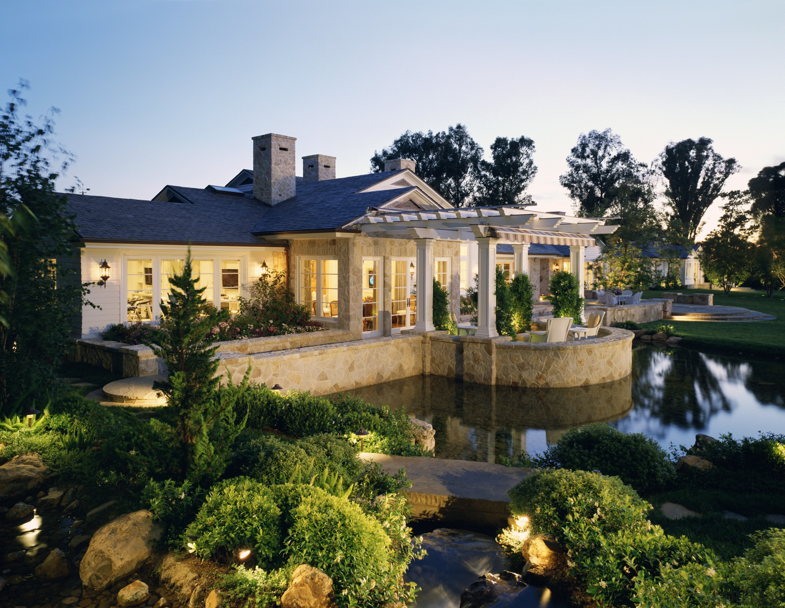 View of exterior features surrounding gardens & pond backyard, cottage, estate, garden, hacienda, home, house, landscape, landscape lighting, landscaping, lighting, mansion, outdoor structure, property, real estate, reflection, residential area, resort, roof, villa, yard