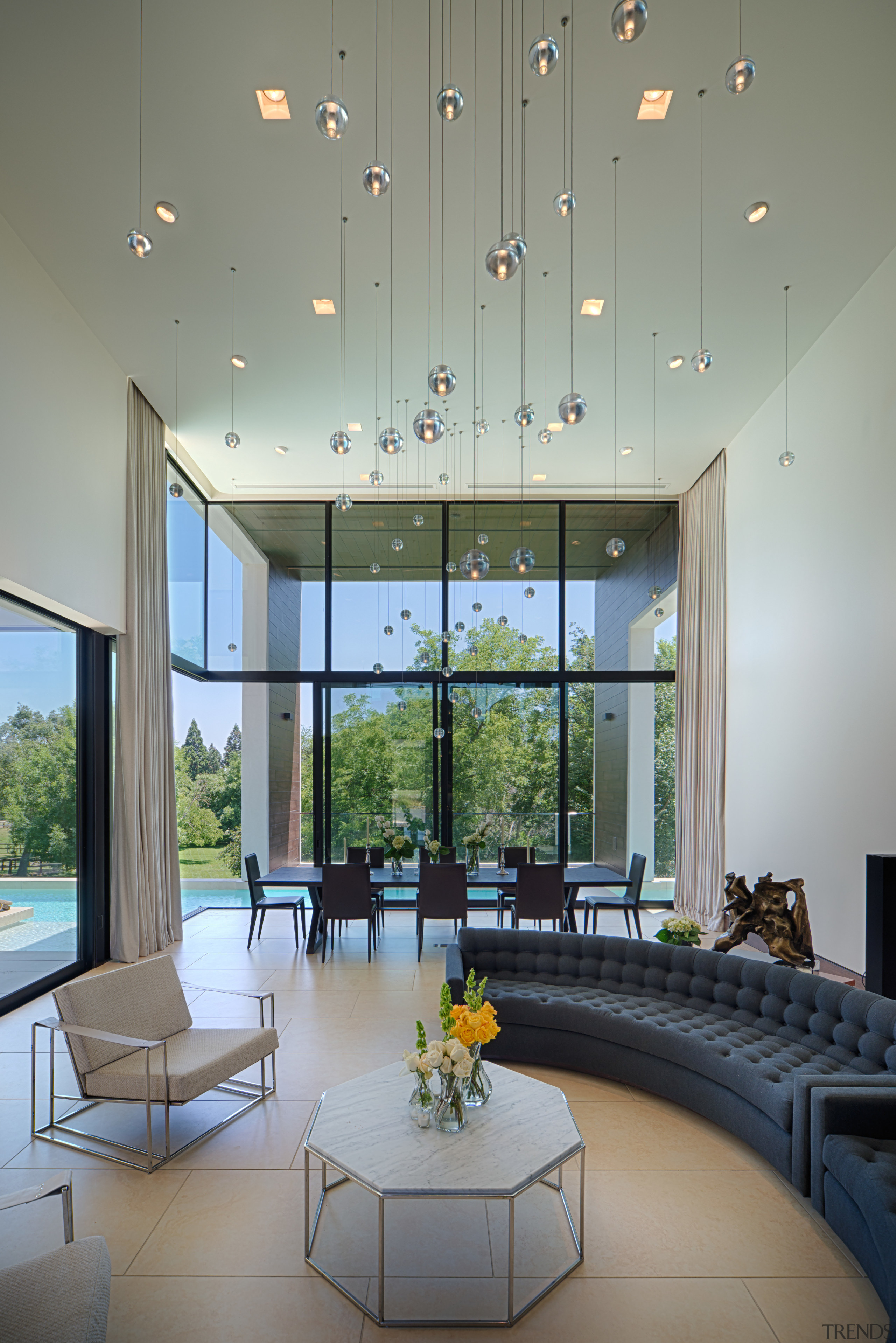 The entry leads directly into a large, two-story architecture, ceiling, daylighting, house, interior design, living room, lobby, window, gray