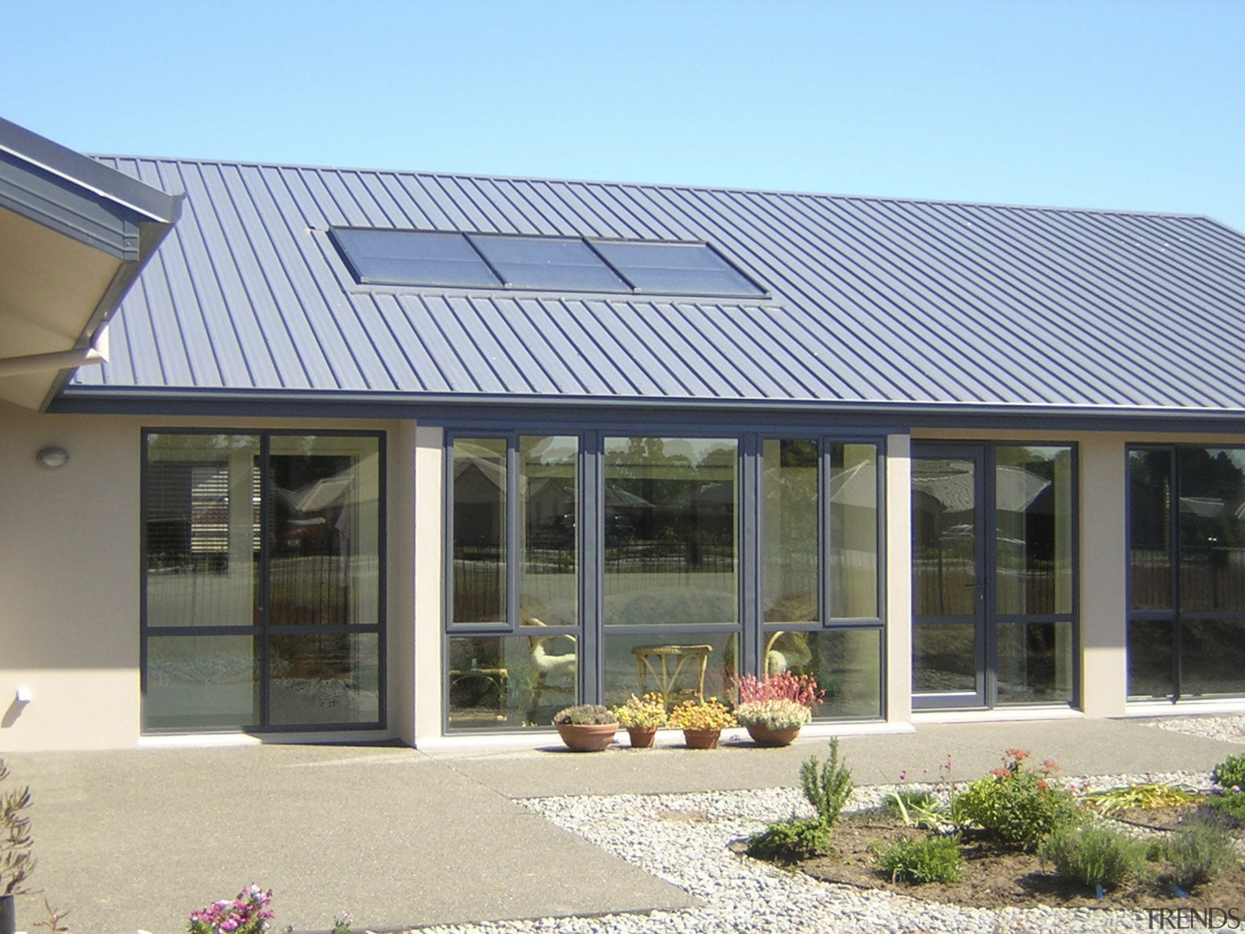 This large home efficiently uses solar energy thanks daylighting, facade, home, house, orangery, real estate, roof, window, gray