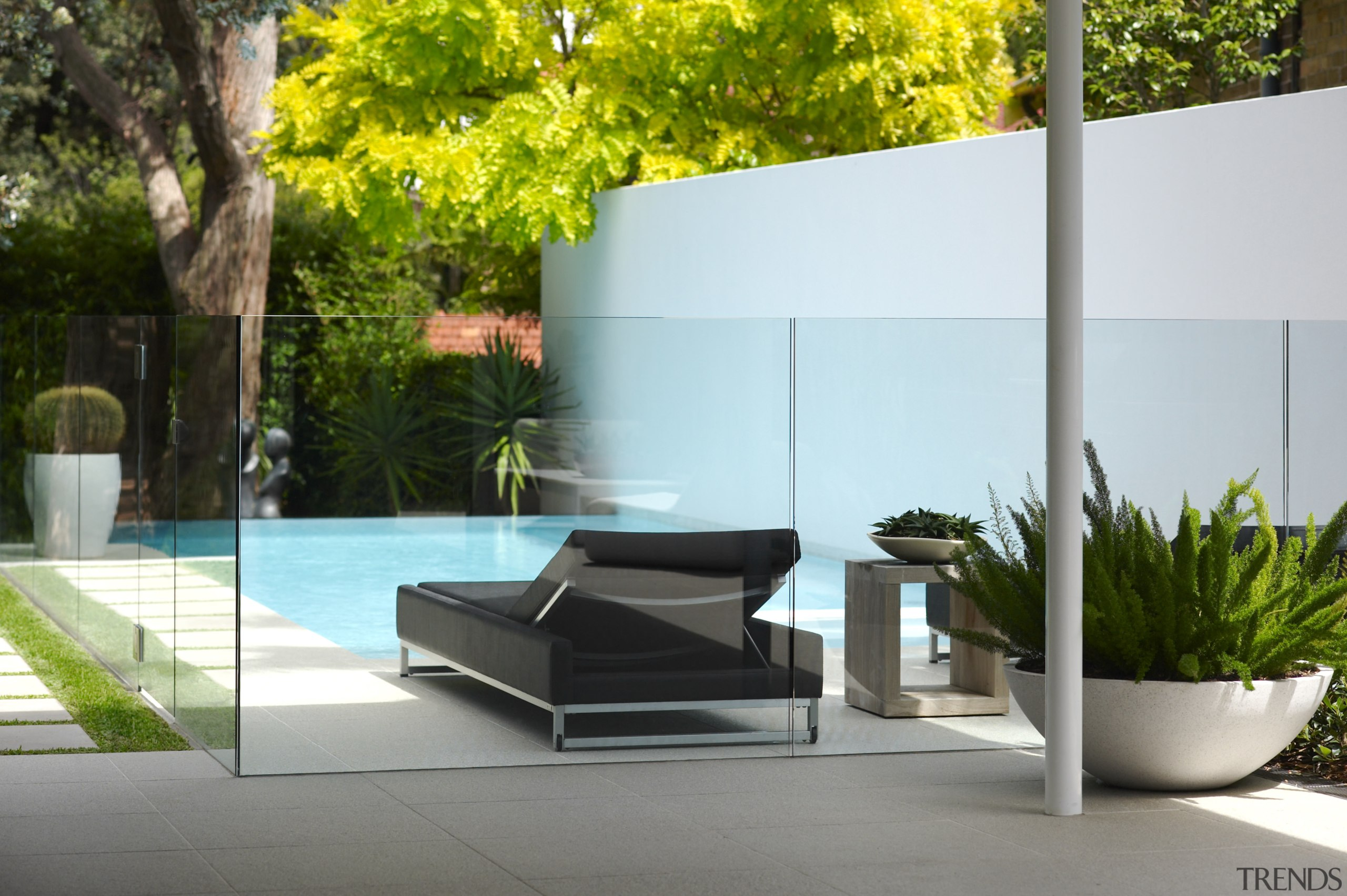 A glass pool fence in this garden ensures architecture, backyard, courtyard, flowerpot, furniture, glass, grass, home, house, interior design, outdoor furniture, plant, property, table, wall, gray, white