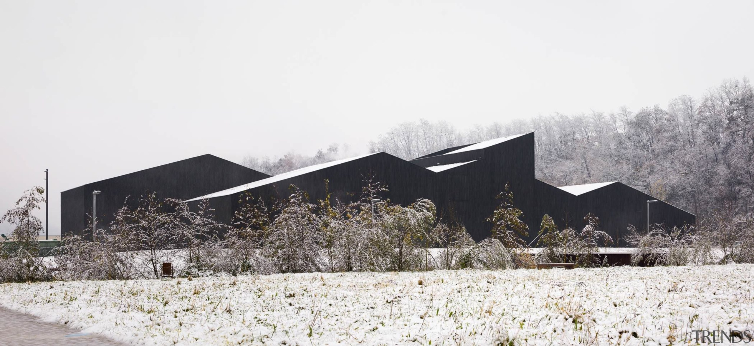 The building almost looks like a rock formation architecture, barn, farmhouse, home, house, snow, tree, winter, white