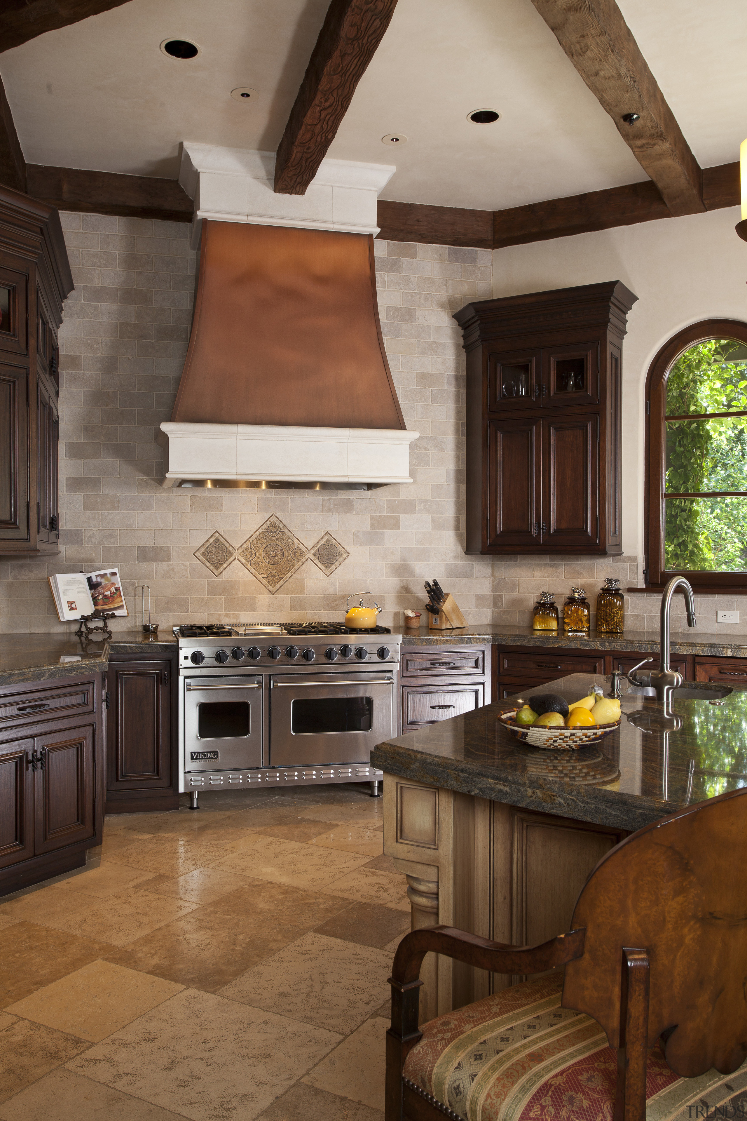 A copper-patina range hood is a centerpiece of cabinetry, ceiling, countertop, cuisine classique, floor, flooring, home appliance, interior design, kitchen, room, brown