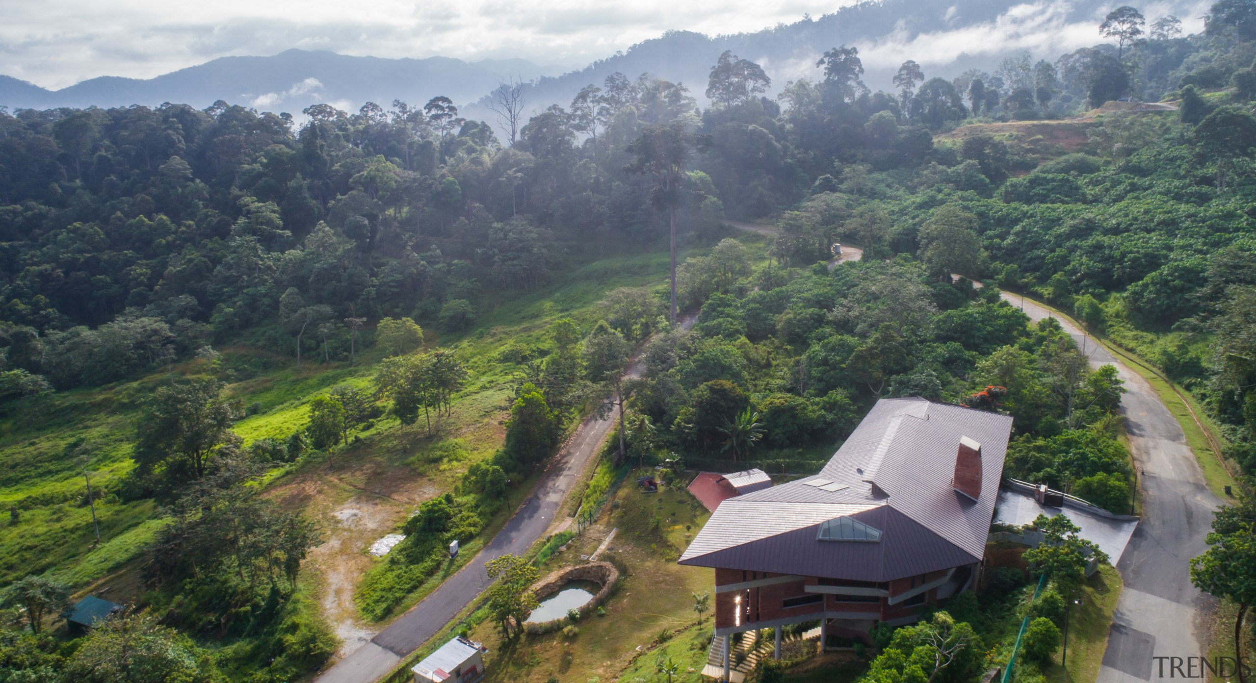 The homeowners approached MJ Kanny Architect to design aerial photography, bird's-eye view, geological phenomenon, highland, hill, hill station, jungle, landscape, mount scenery, mountain, mountain village, mountainous landforms, rainforest, rural area, sky, vegetation, village, gray