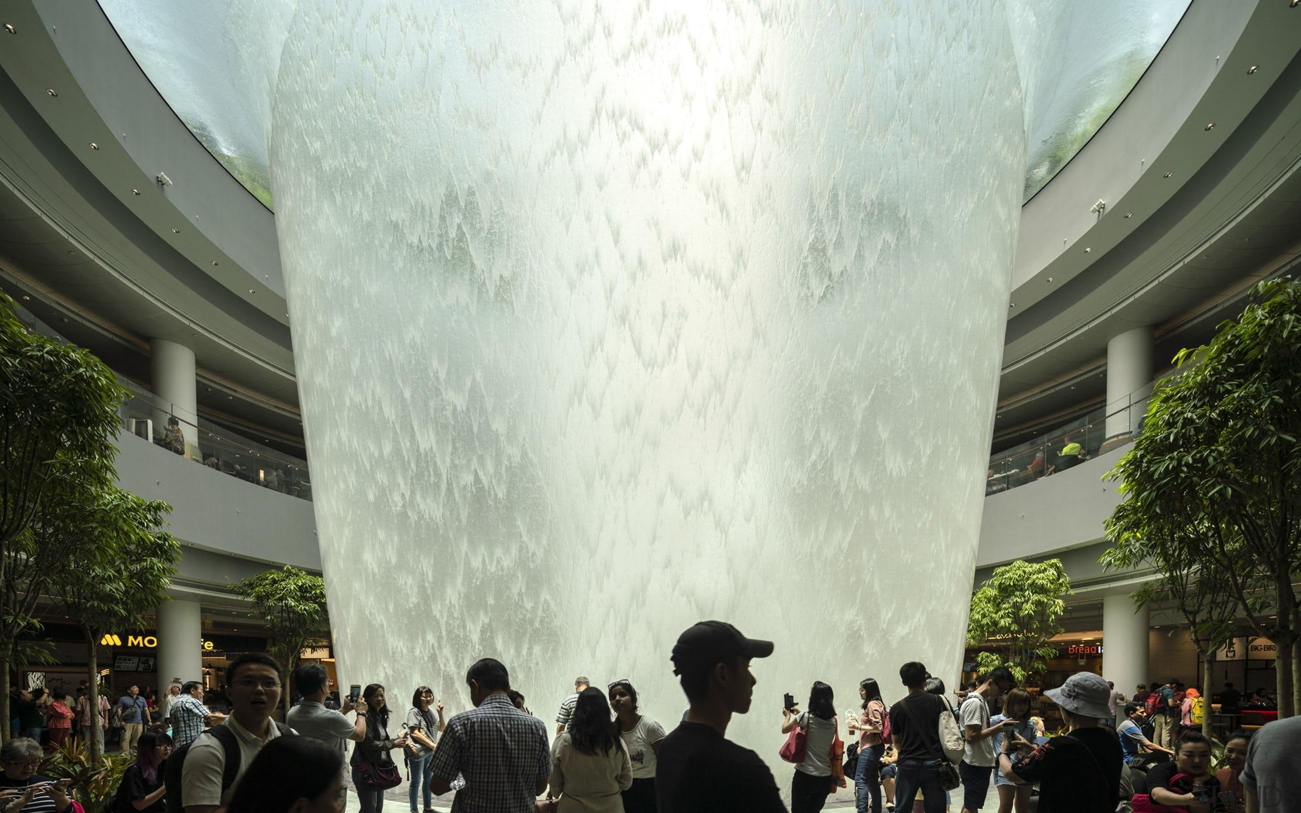 Jewel Changi Airport boasts a hub with quite architecture, crowd, event, fountain, tree, white