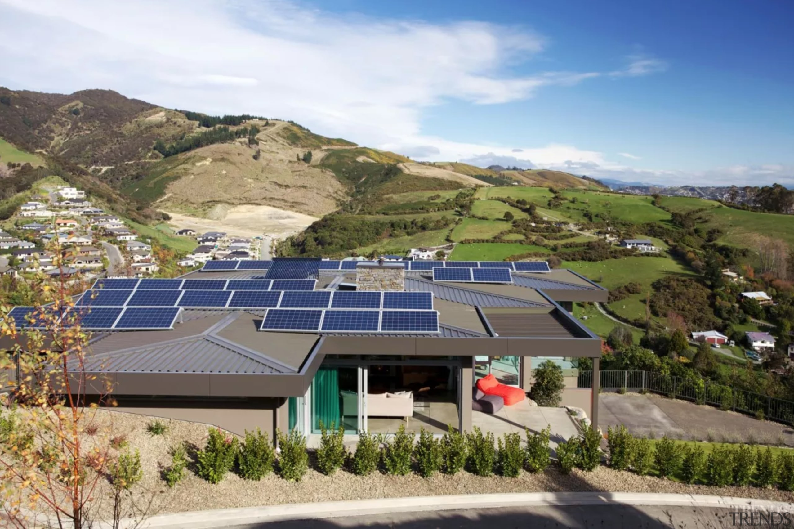 An array of solar panels powers this green architecture, building, estate, highland, hill station, home, house, mountain, mountain range, mountainous landforms, property, real estate, residential area, roof, sky, slope, solar energy, solar panel, solar power, sunlight, technology, brown