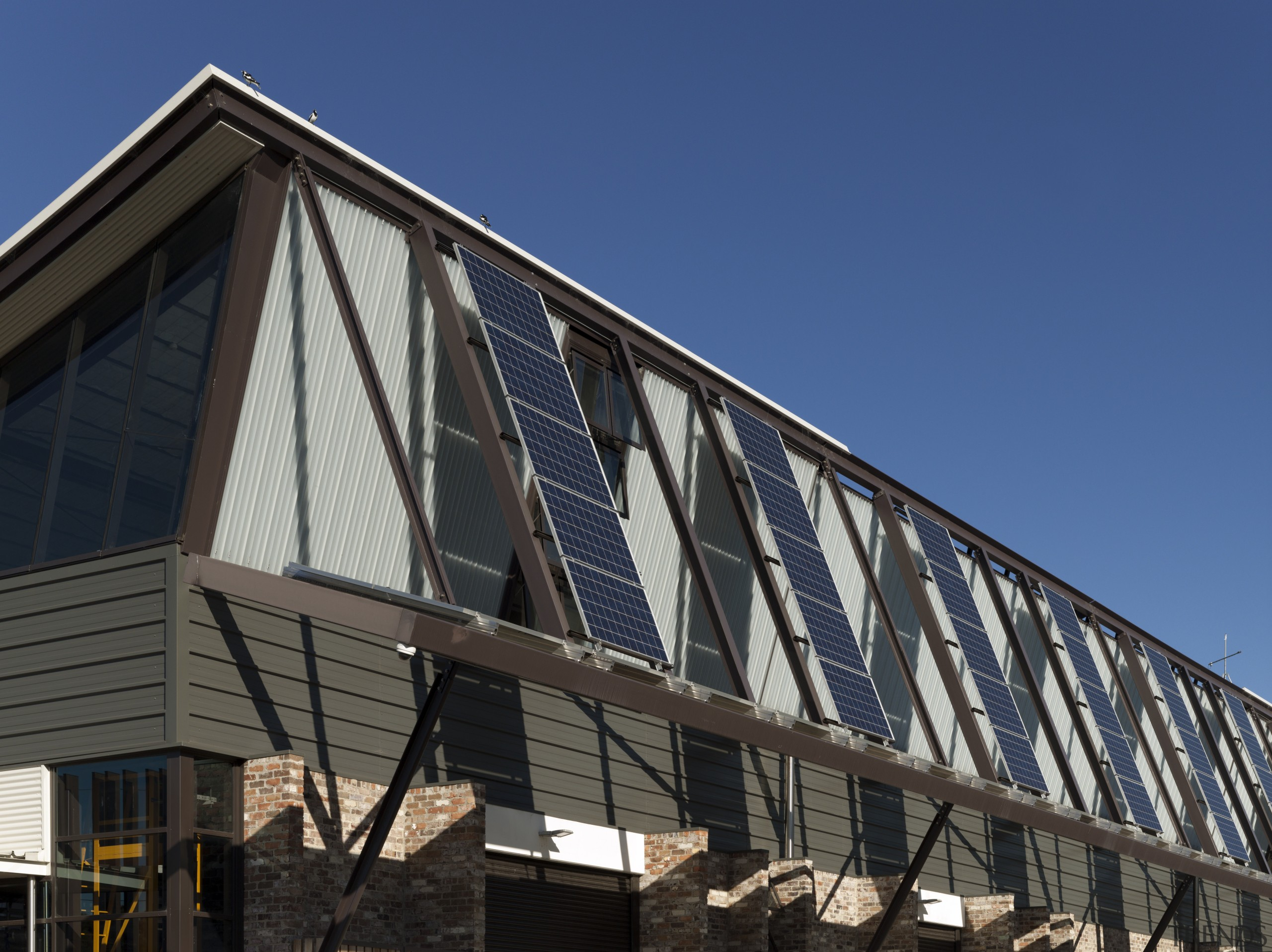The north-facing photovoltaic array on the high-bay laboratory architecture, building, commercial building, corporate headquarters, daylighting, daytime, facade, home, house, roof, siding, sky, structure, window, blue, black