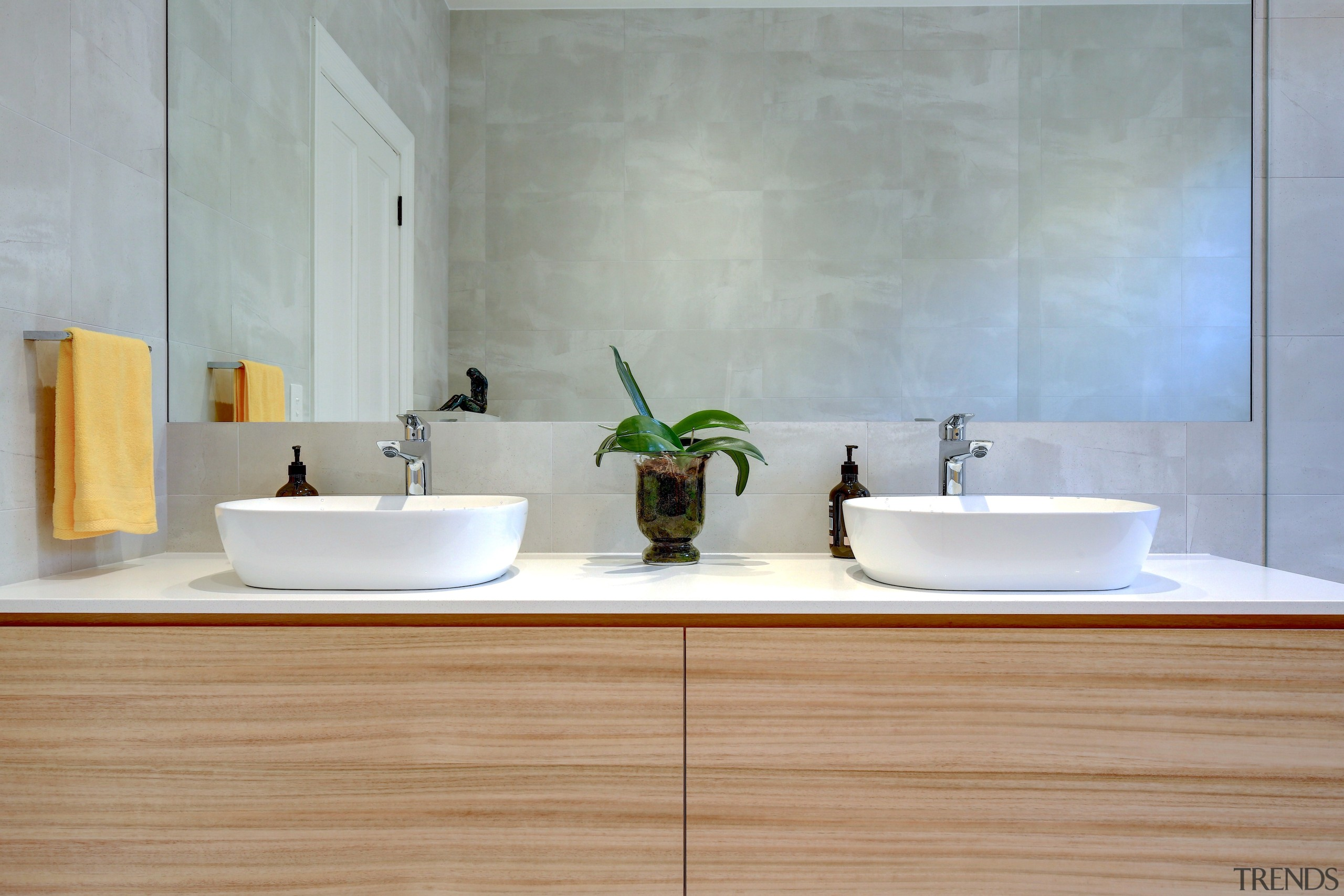 A large mirror was a key part of architecture, bathroom, bathroom sink, ceramic, countertop, floor, flooring, hardwood, interior design, marble, material property, plumbing fixture, property, room, sink, tap, tile, wall, wood, gray
