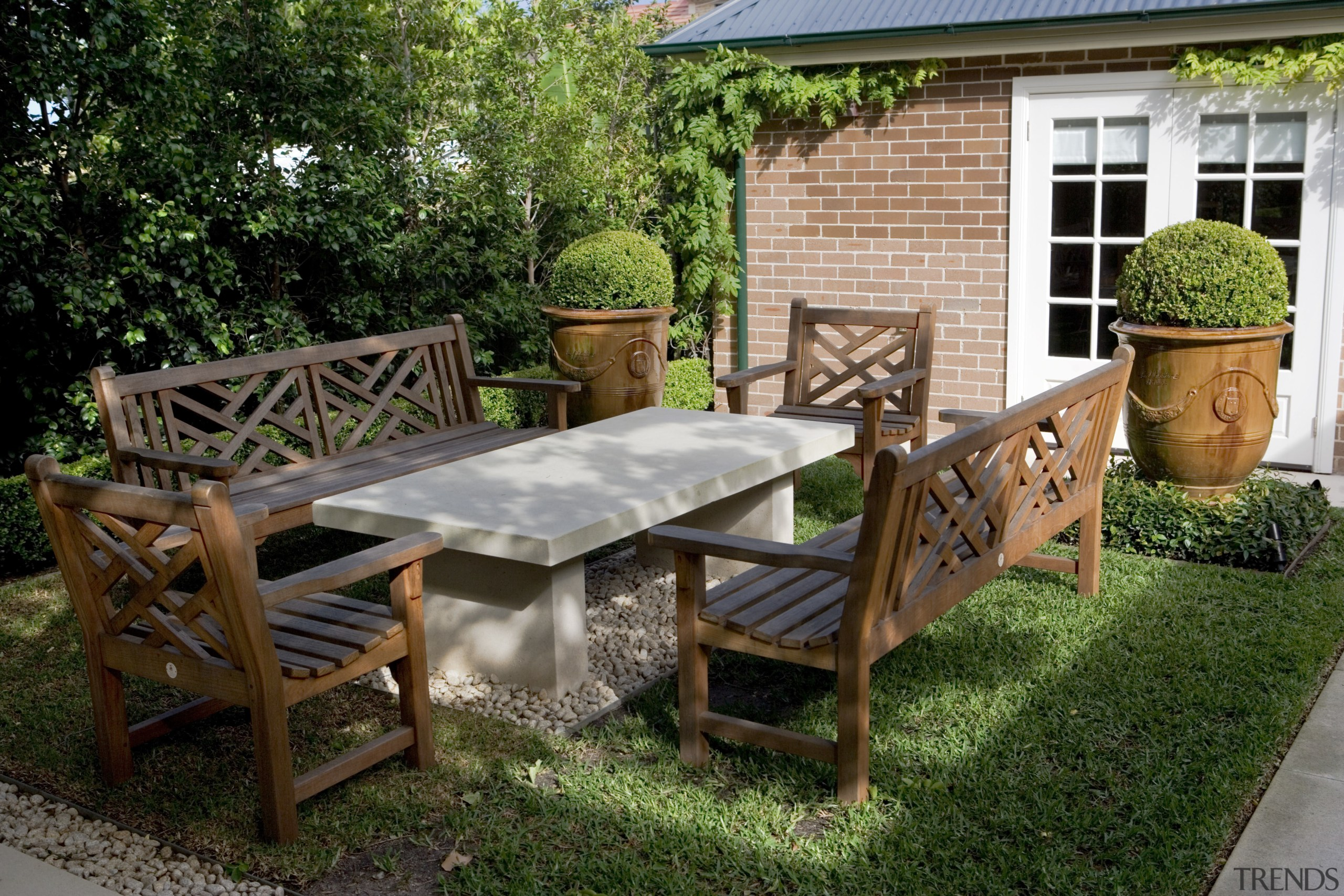 Seating is placed around the garden to provide backyard, chair, furniture, garden, outdoor furniture, outdoor structure, patio, plant, table, yard, brown