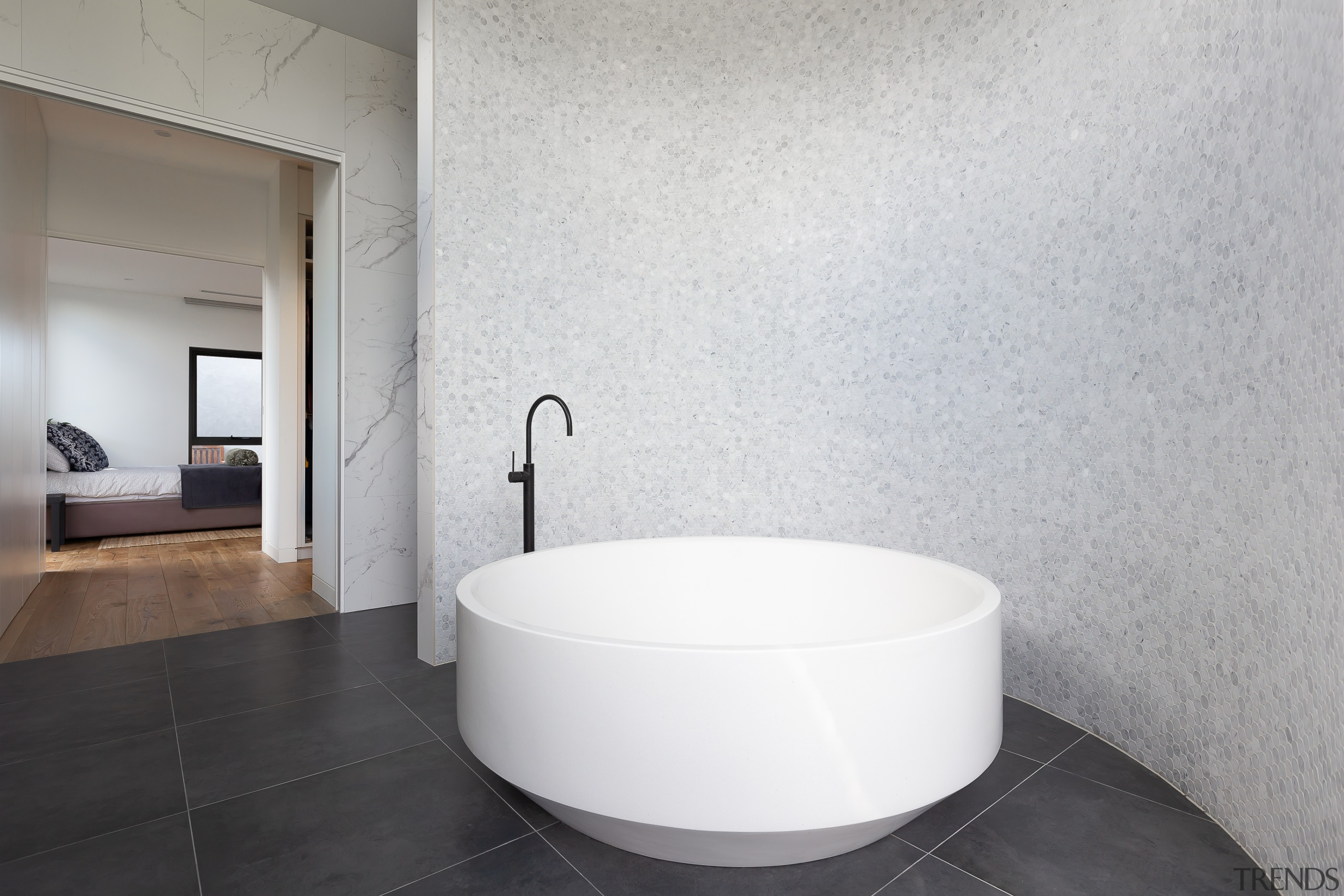 The feature curved wall in this master ensuite gray, white