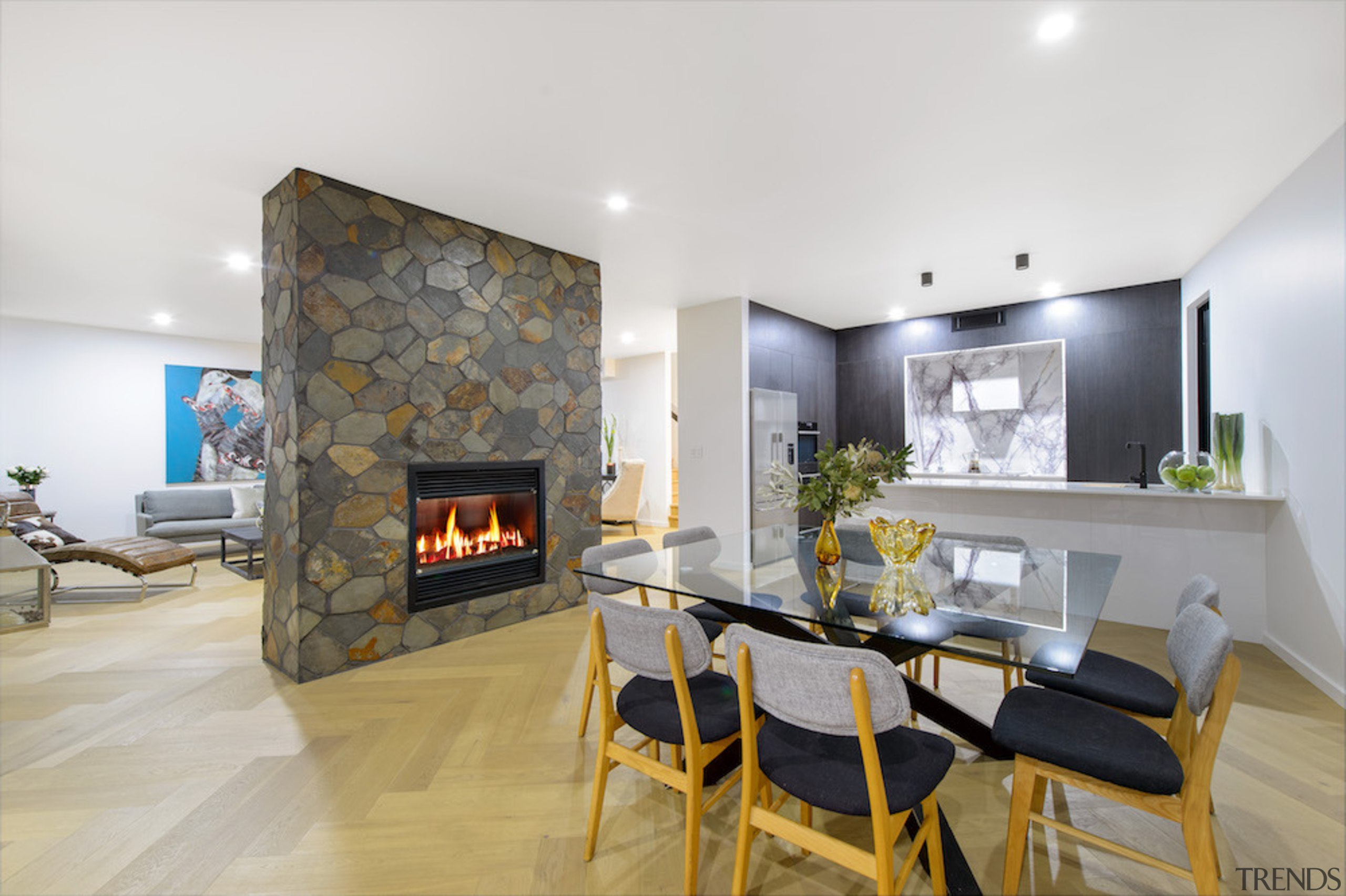 Stone fire surround connects with marble kitchen across building, design, dining room, estate, fireplace, floor, furniture, hearth, home, house, interior design, living room, property, real estate, room, table, white