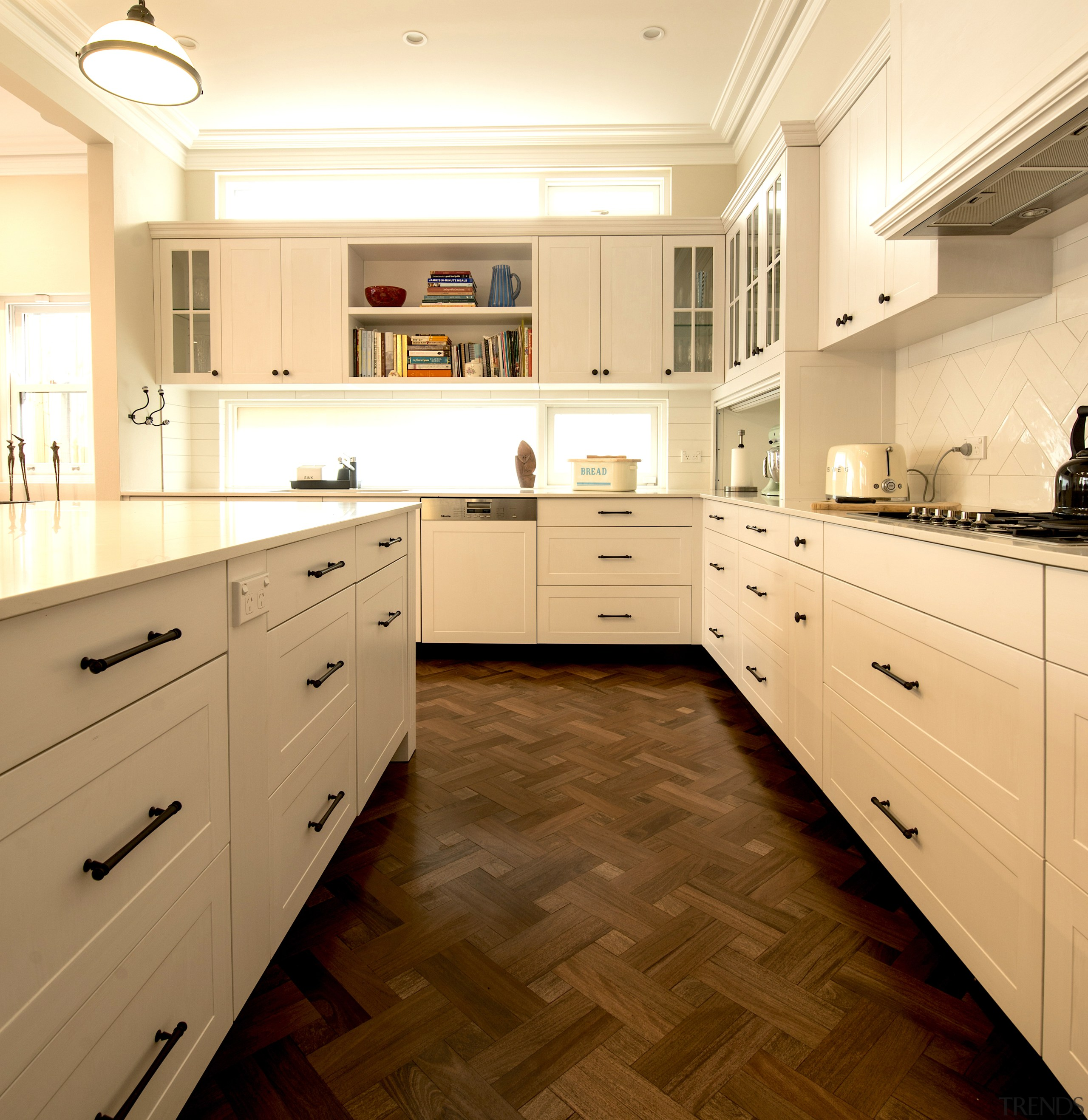 Shaker-style doors with decorative black handles are both architecture, building, cabinetry, ceiling, countertop, cupboard, drawer, floor, flooring, furniture, home, house, interior design, kitchen, lighting, material property, property, real estate, room, sink, tile, wood flooring, yellow, orange, brown