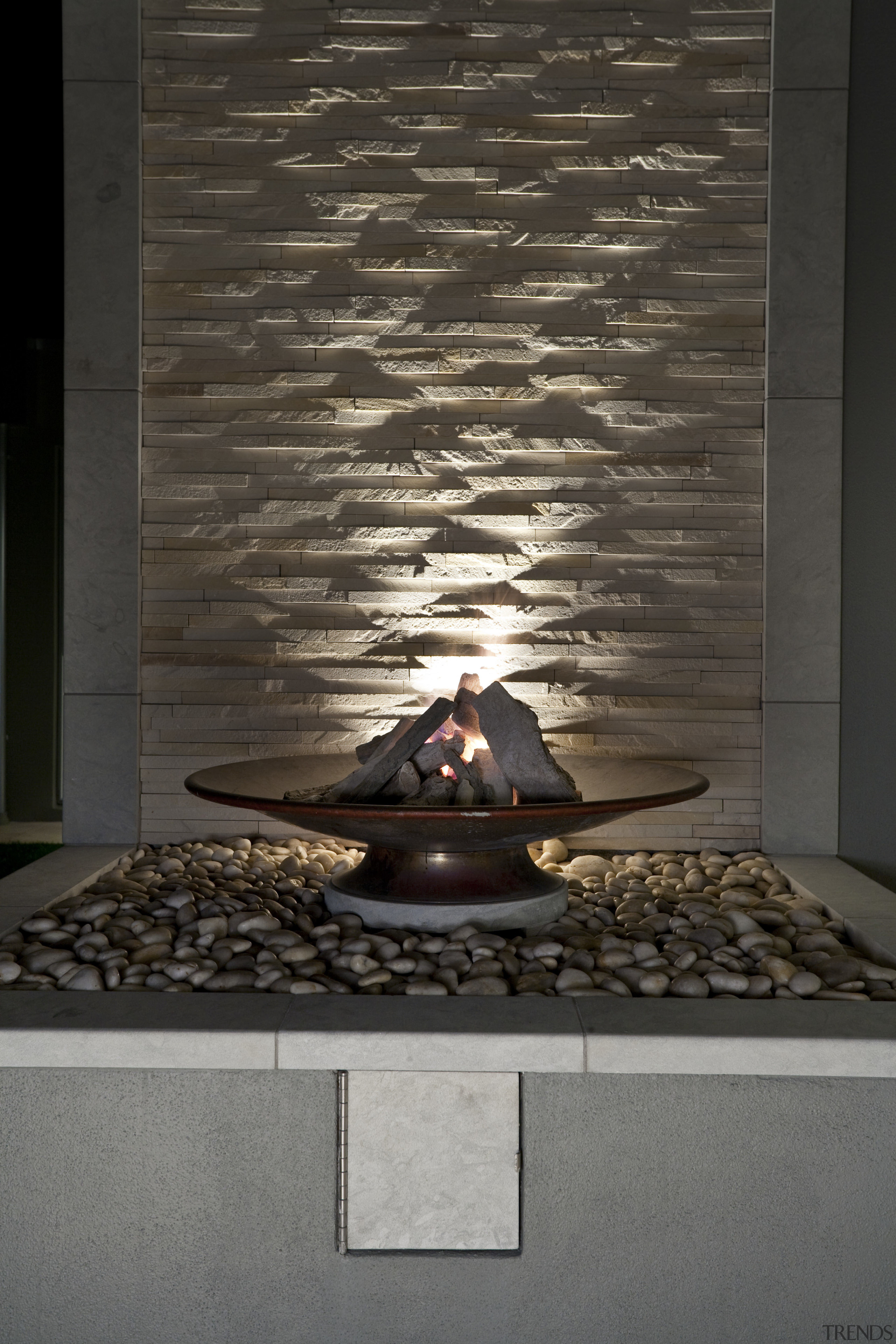 View of sleek poolscape with textured stone wall, floor, flooring, hearth, wall, black, gray