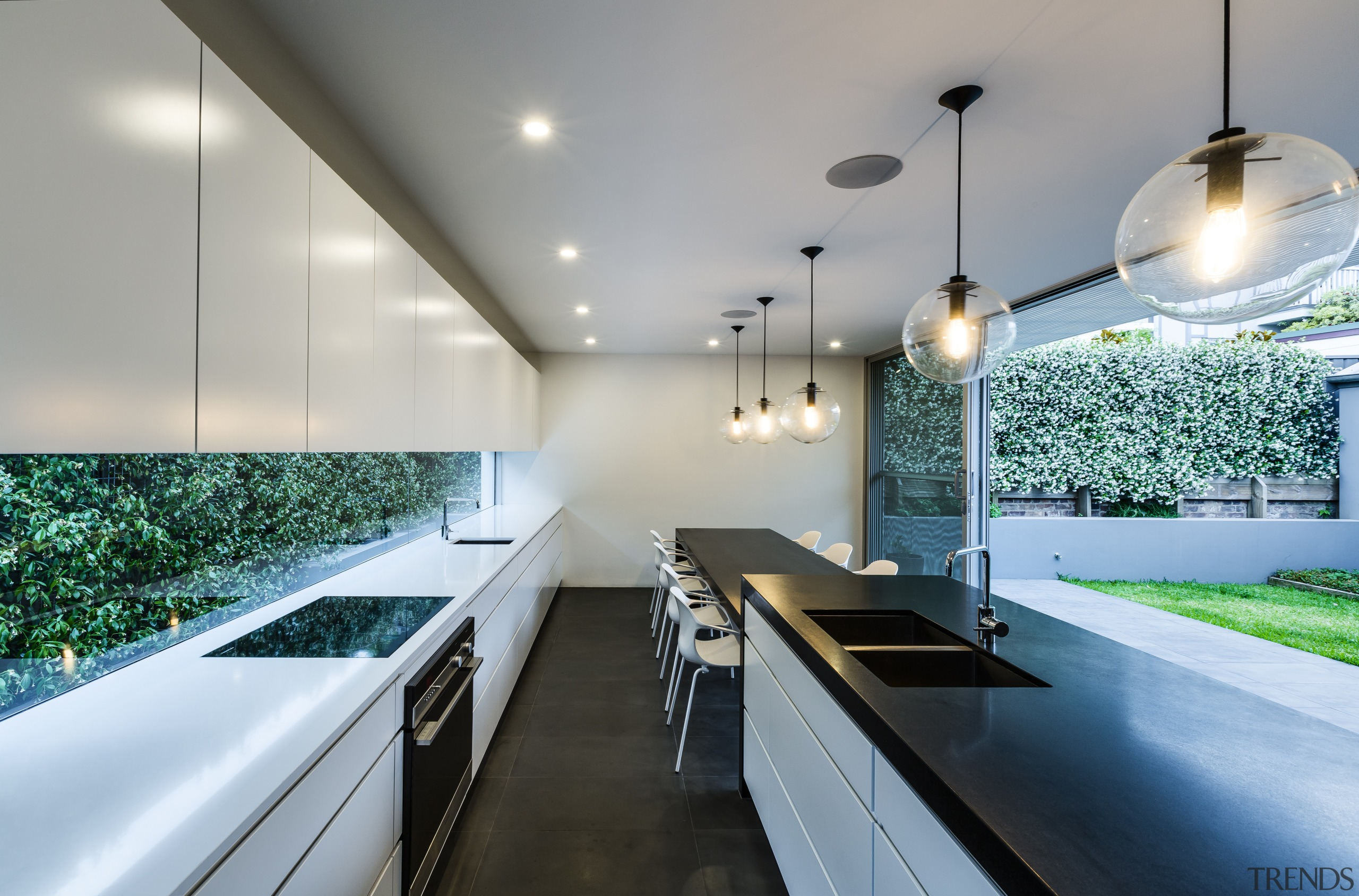 Parallel cabinets reinforce the strong horizontality of this architecture, ceiling, countertop, daylighting, house, interior design, kitchen, lighting, real estate, gray