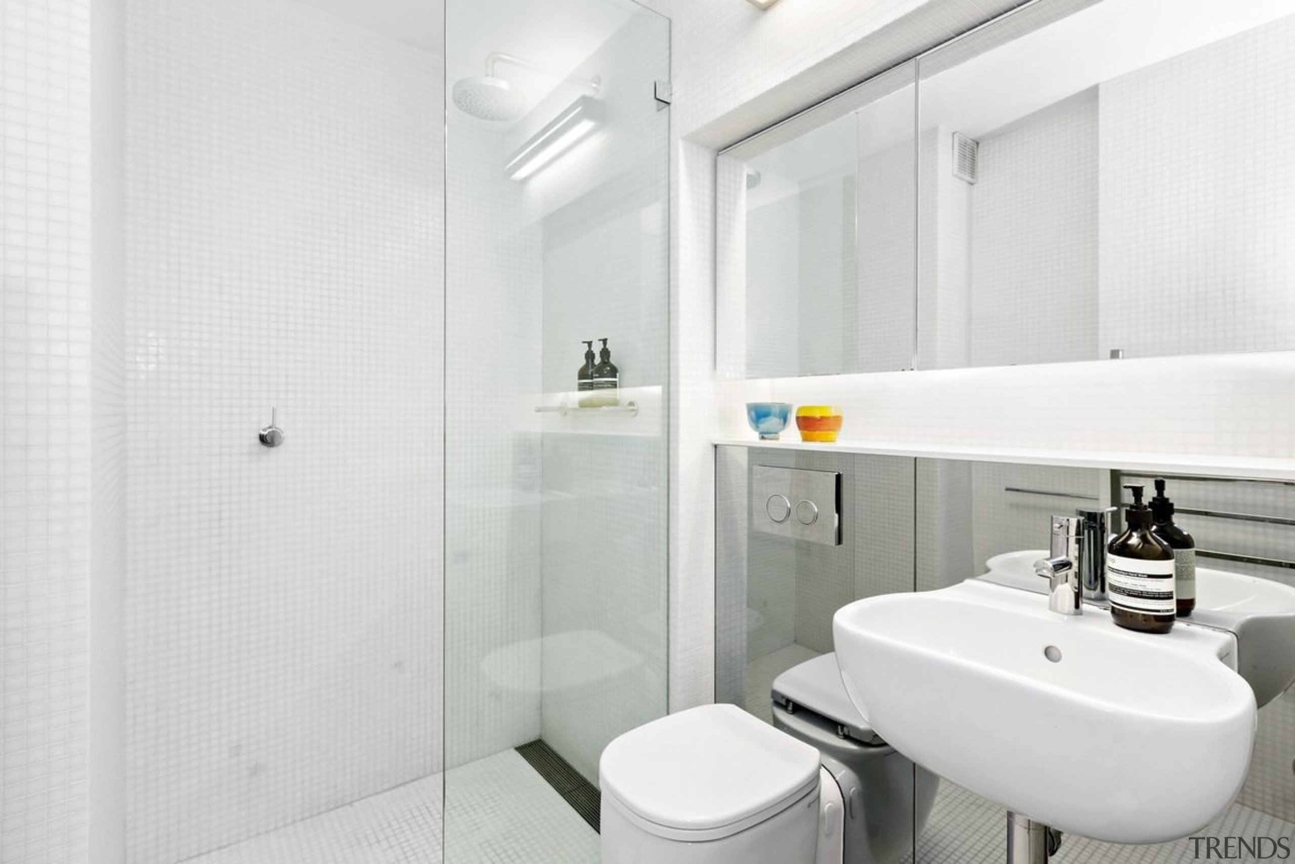 A large mirrored wall is broken up by bathroom, bathroom accessory, interior design, plumbing fixture, product design, property, room, tap, toilet seat, white