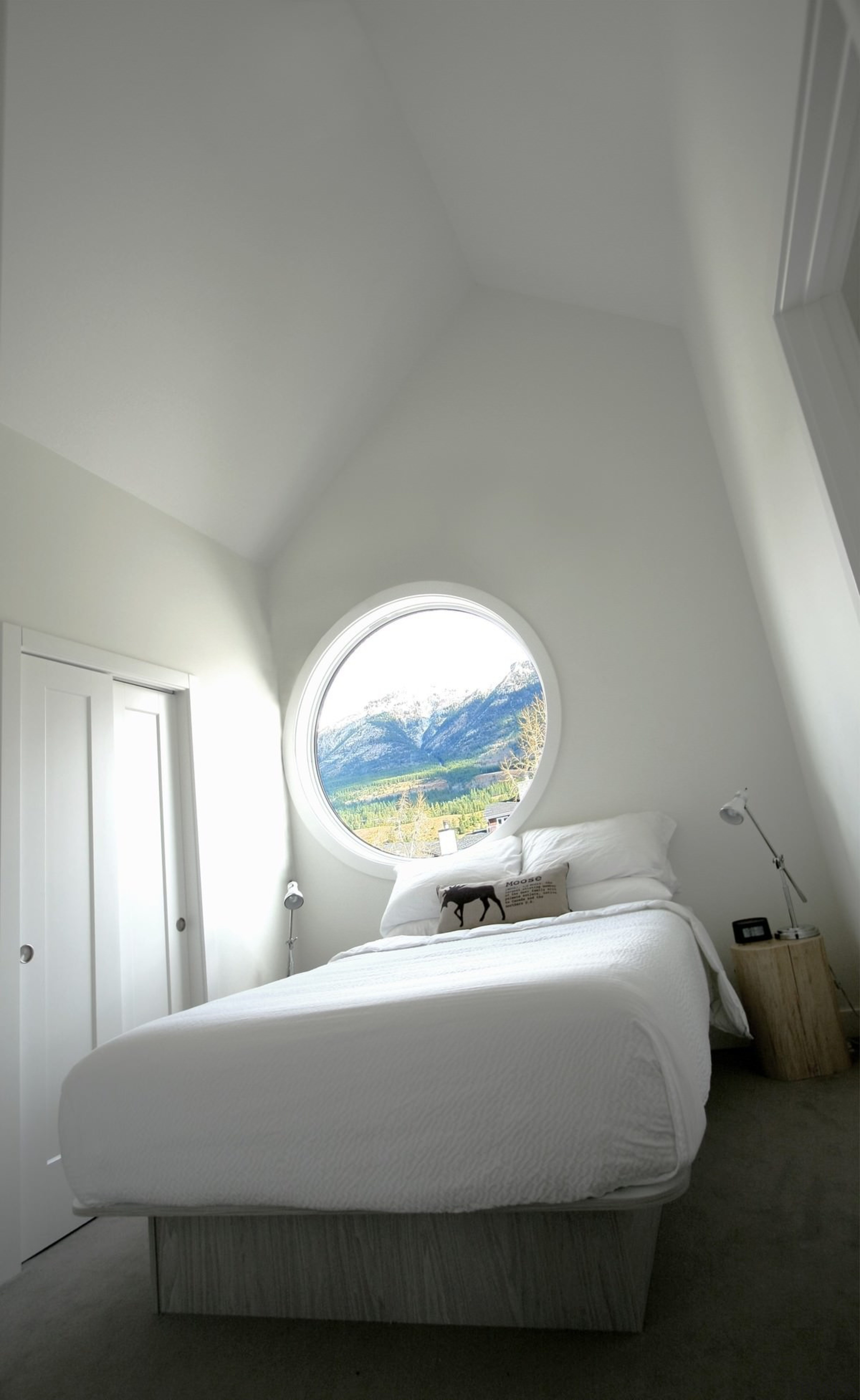 The circular window frames the mountain landscape - architecture, bed, bedroom, ceiling, daylighting, furniture, home, house, interior design, light fixture, lighting, product design, room, wall, window, gray