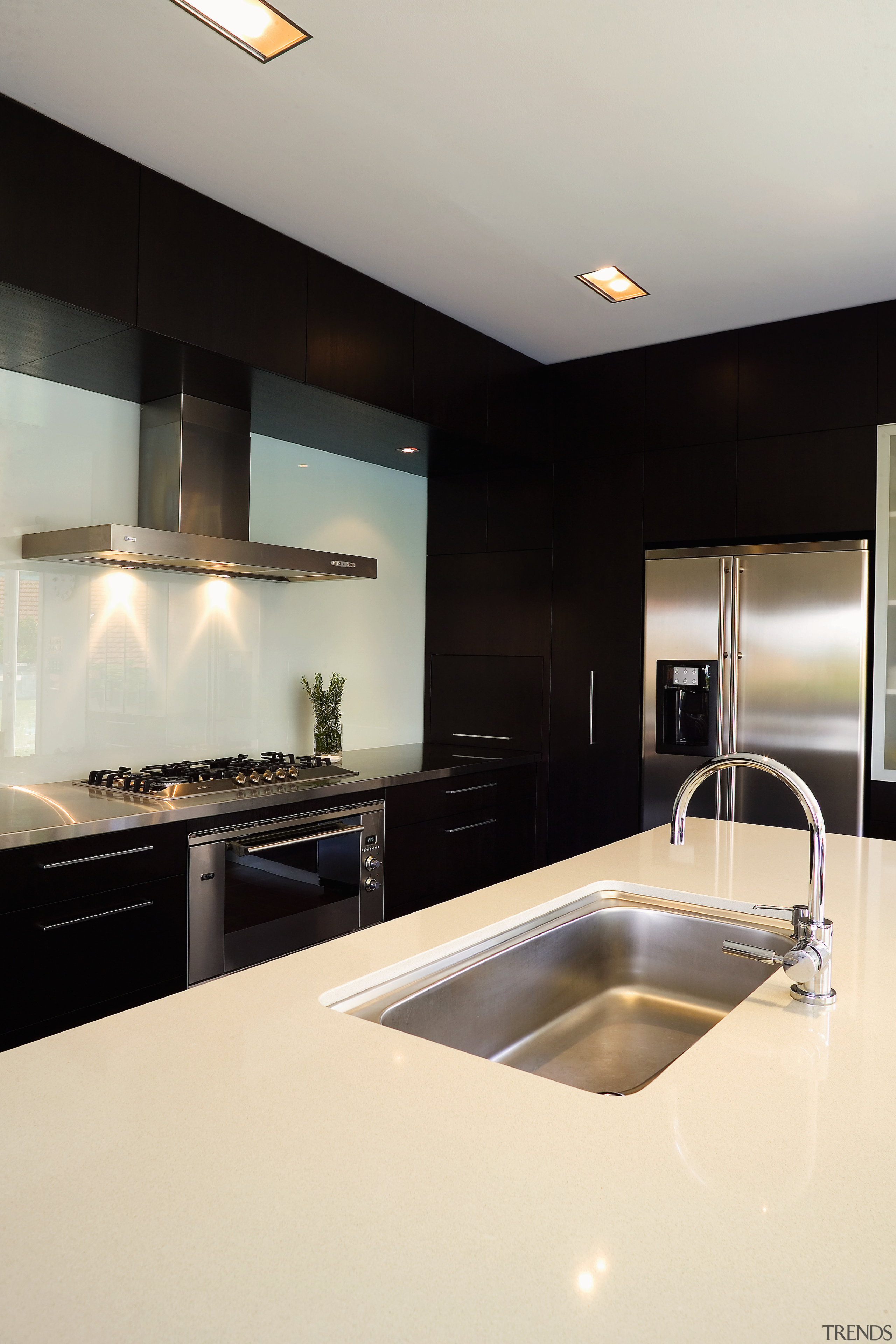 A view of athis kitchen featuring mahogany and countertop, interior design, kitchen, room, sink, white, black