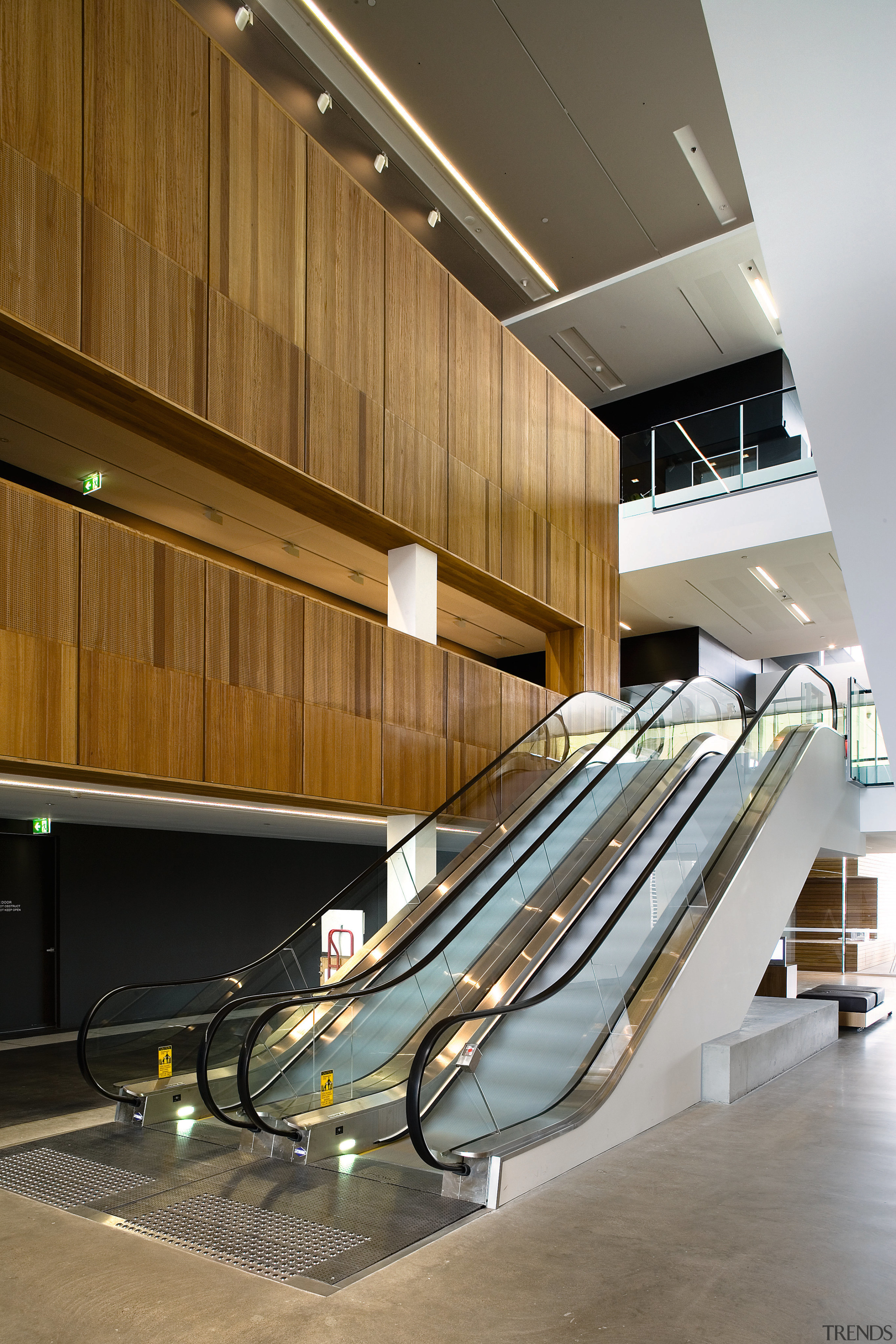 A view of some esculators from Liftronic. - architecture, daylighting, floor, handrail, interior design, stairs, wood, brown, gray