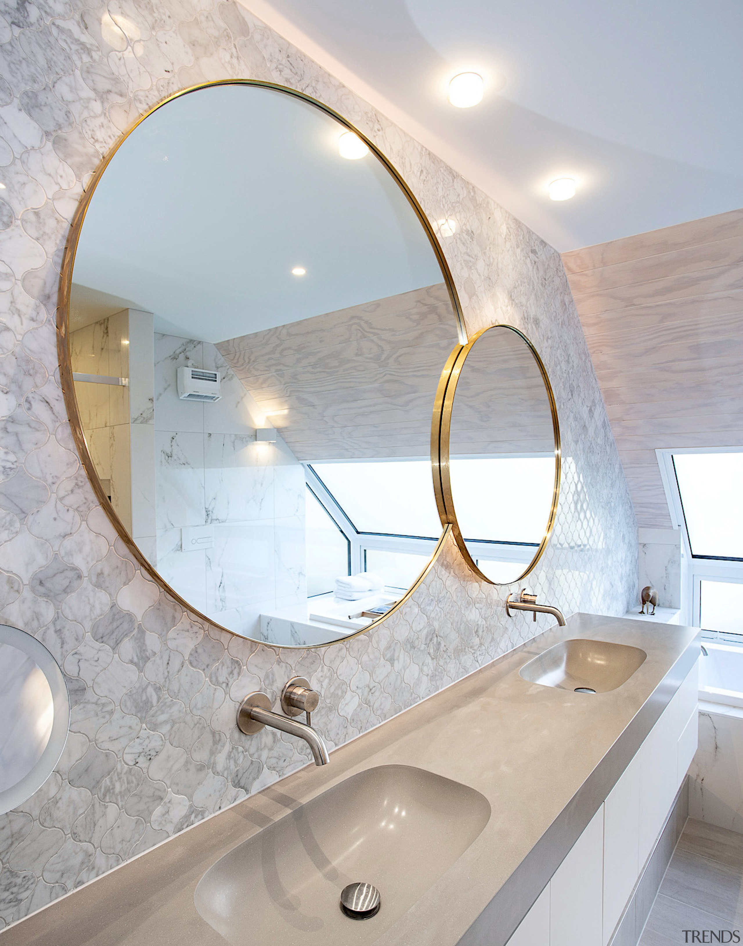 Two mirrors co-joined by one brass frame create architecture, bathroom, bathroom sink, ceiling, daylighting, floor, home, house, interior design, lighting, marble, mirror, plumbing fixture, property, real estate, room, sink, tap, tile, gray