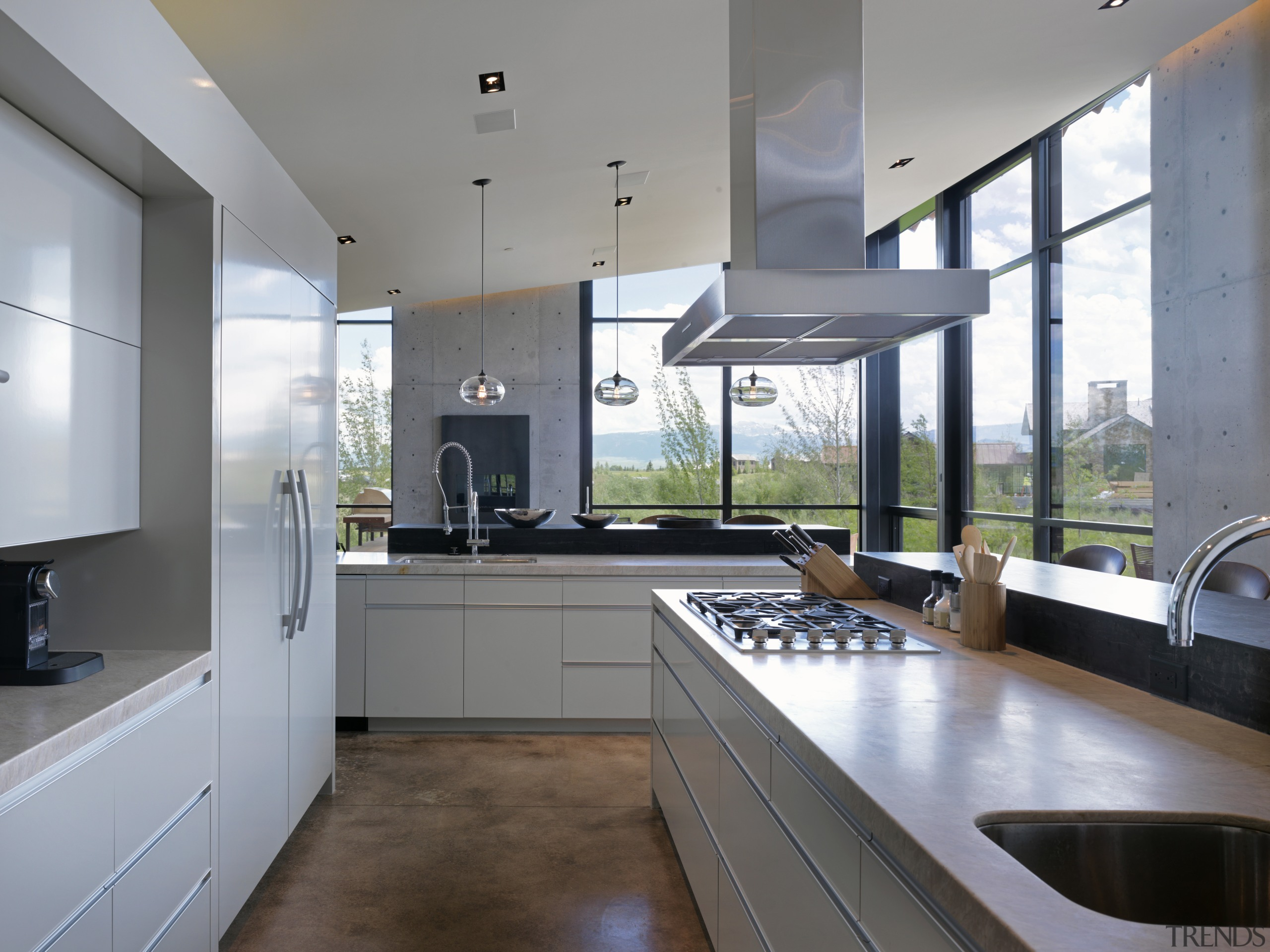 The ceiling in this modern mountain home rises countertop, daylighting, interior design, kitchen, real estate, gray
