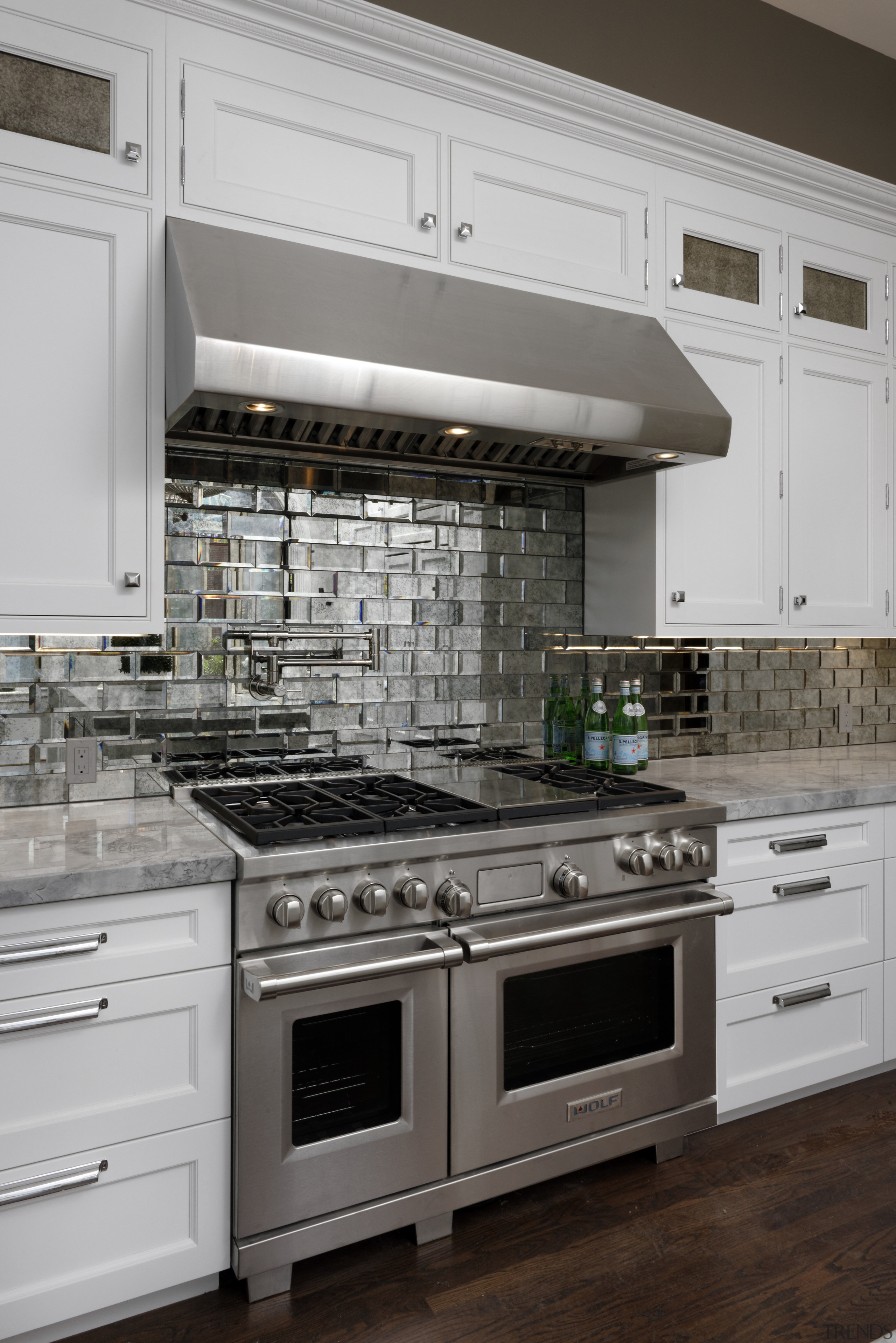 Antiqued bevelled mirror tiles are a feature of cabinetry, countertop, cuisine classique, floor, flooring, home appliance, kitchen, kitchen appliance, kitchen stove, major appliance, room, gray, black