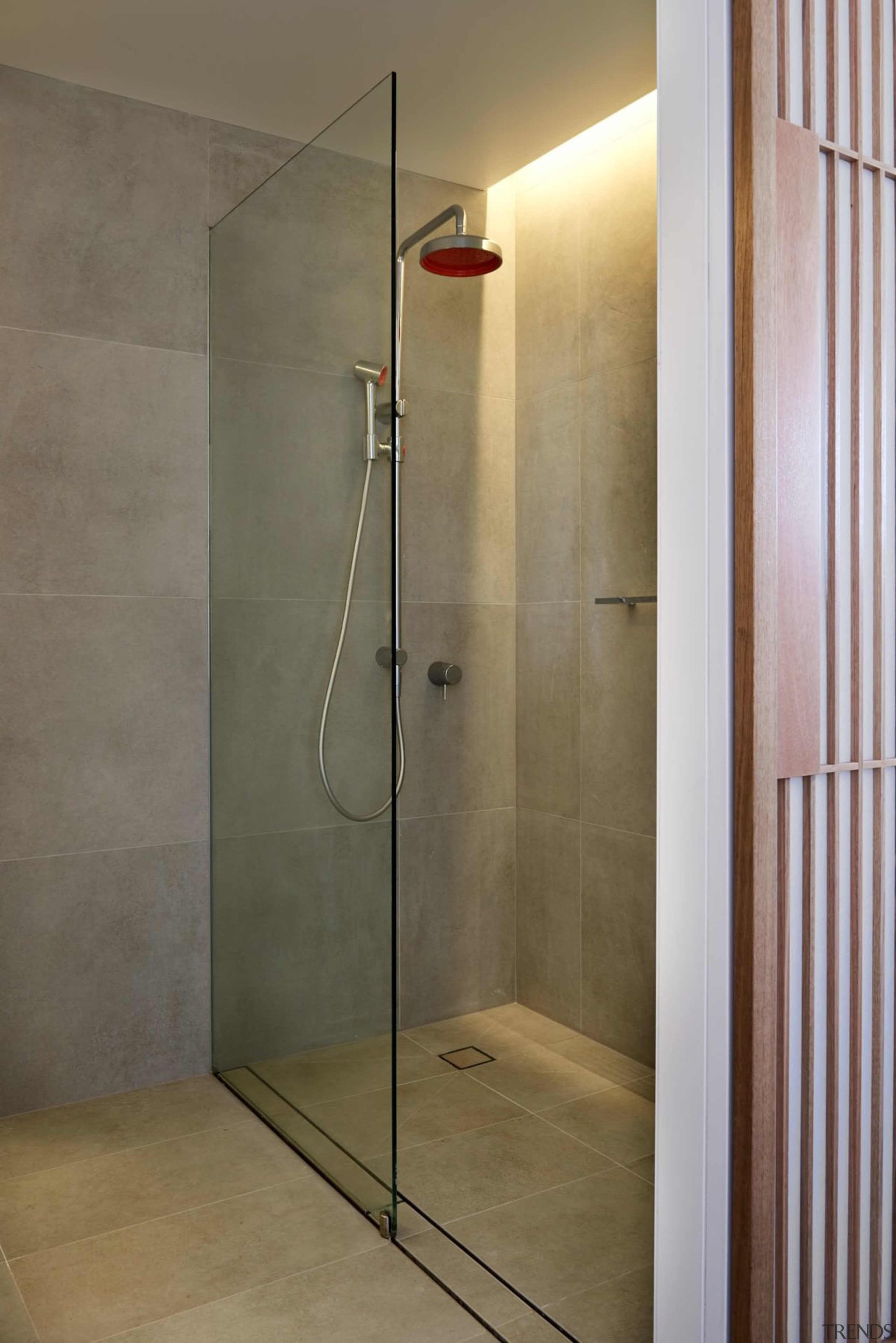 The bathroom has tiles running into the shower angle, bathroom, floor, glass, plumbing fixture, shower, shower door, tile, wall, gray, brown