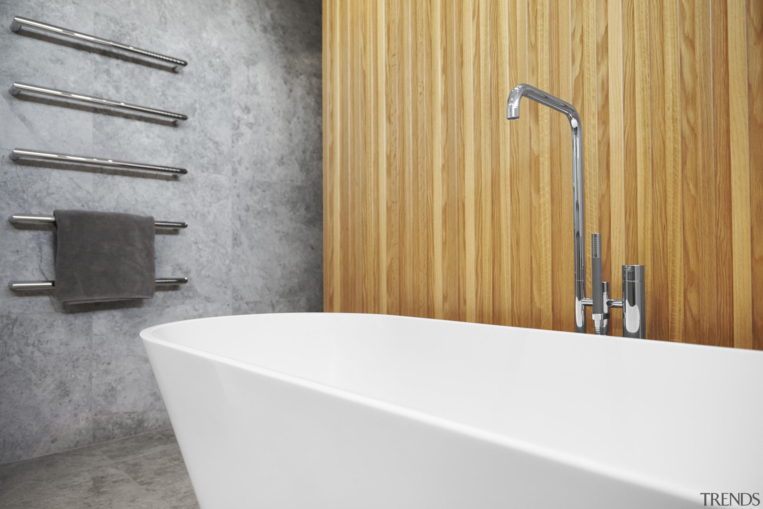 The sculptural bath tub is set off by bathroom, bathroom sink, plumbing fixture, sink, tap, tile, wall, white, gray, orange