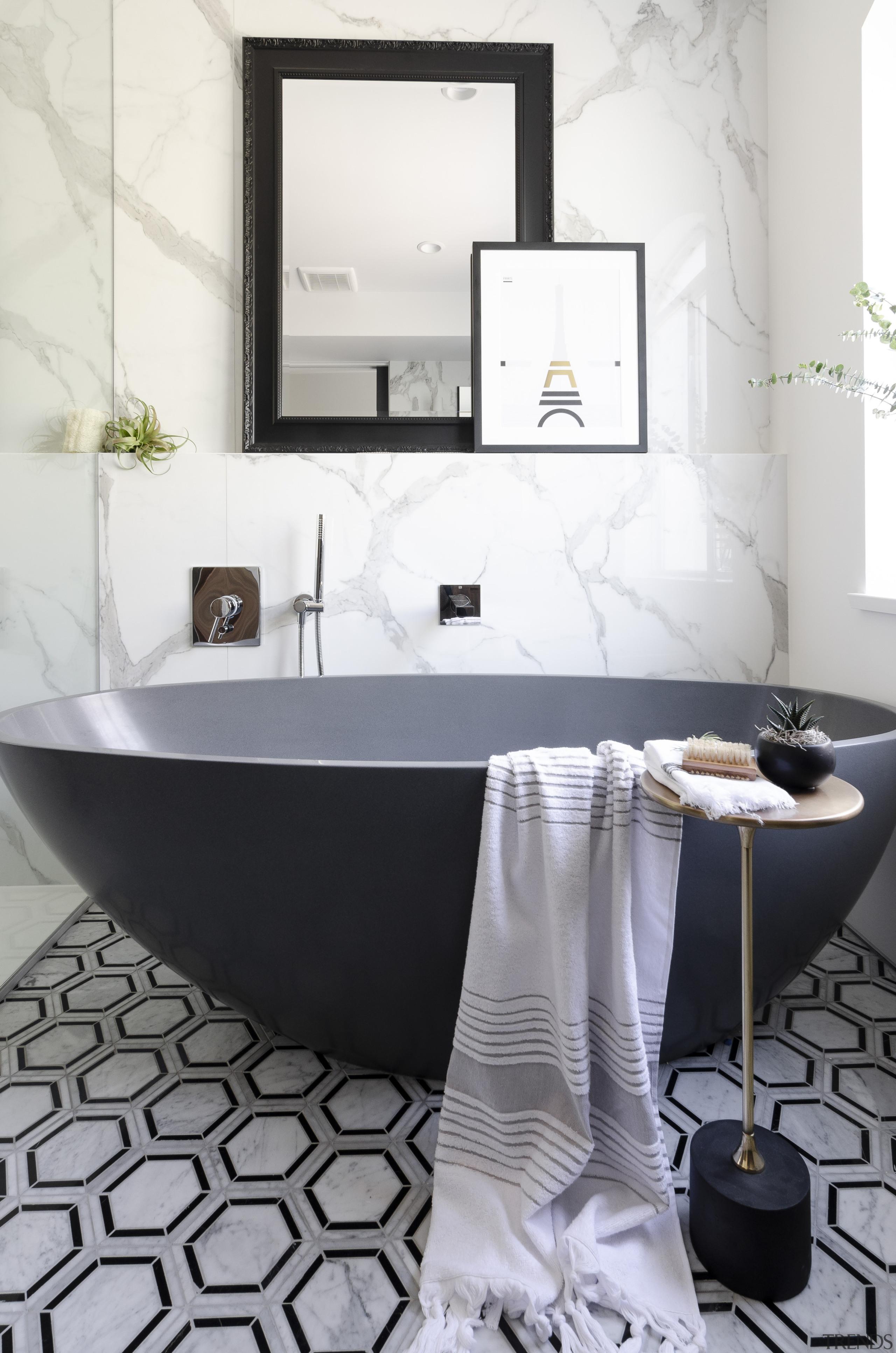 A honed bluestone freestanding tub adds a modern