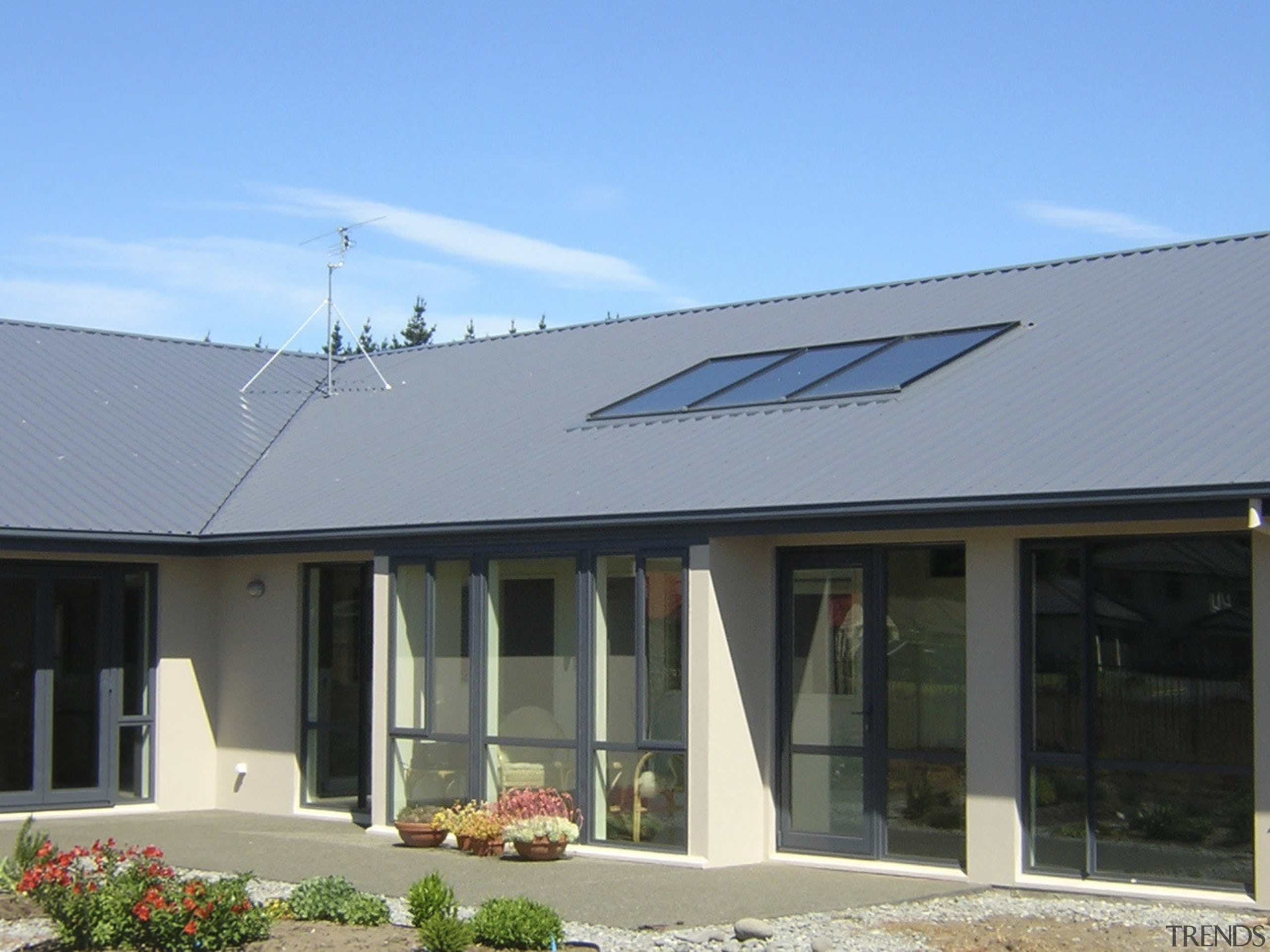 This large home efficiently uses solar energy thanks daylighting, facade, home, house, property, real estate, roof, siding, window, teal