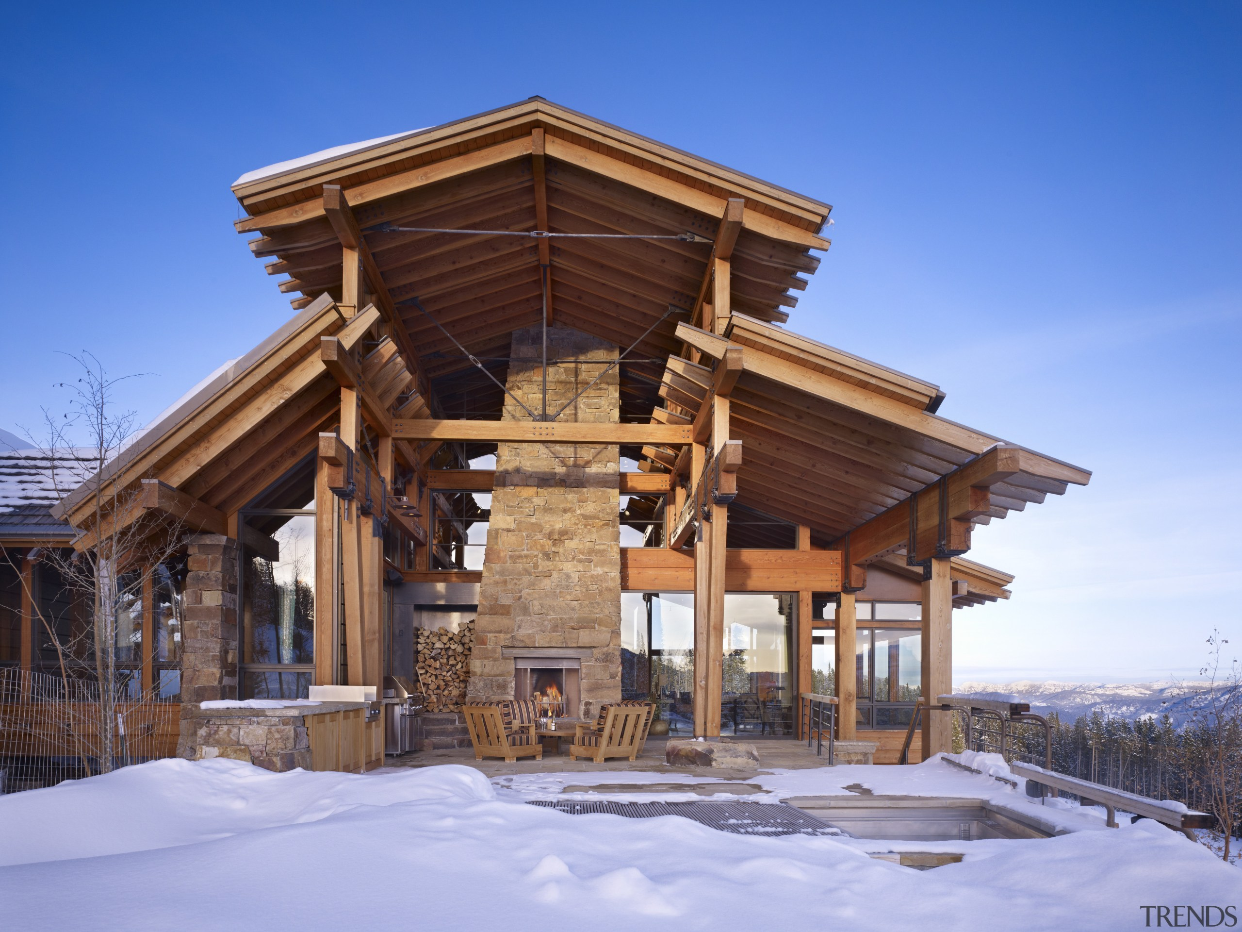 An exoskeleton of chunky wood beams and extended cottage, home, house, hut, log cabin, outdoor structure, property, real estate, roof, shed, siding, snow, winter, wood, teal