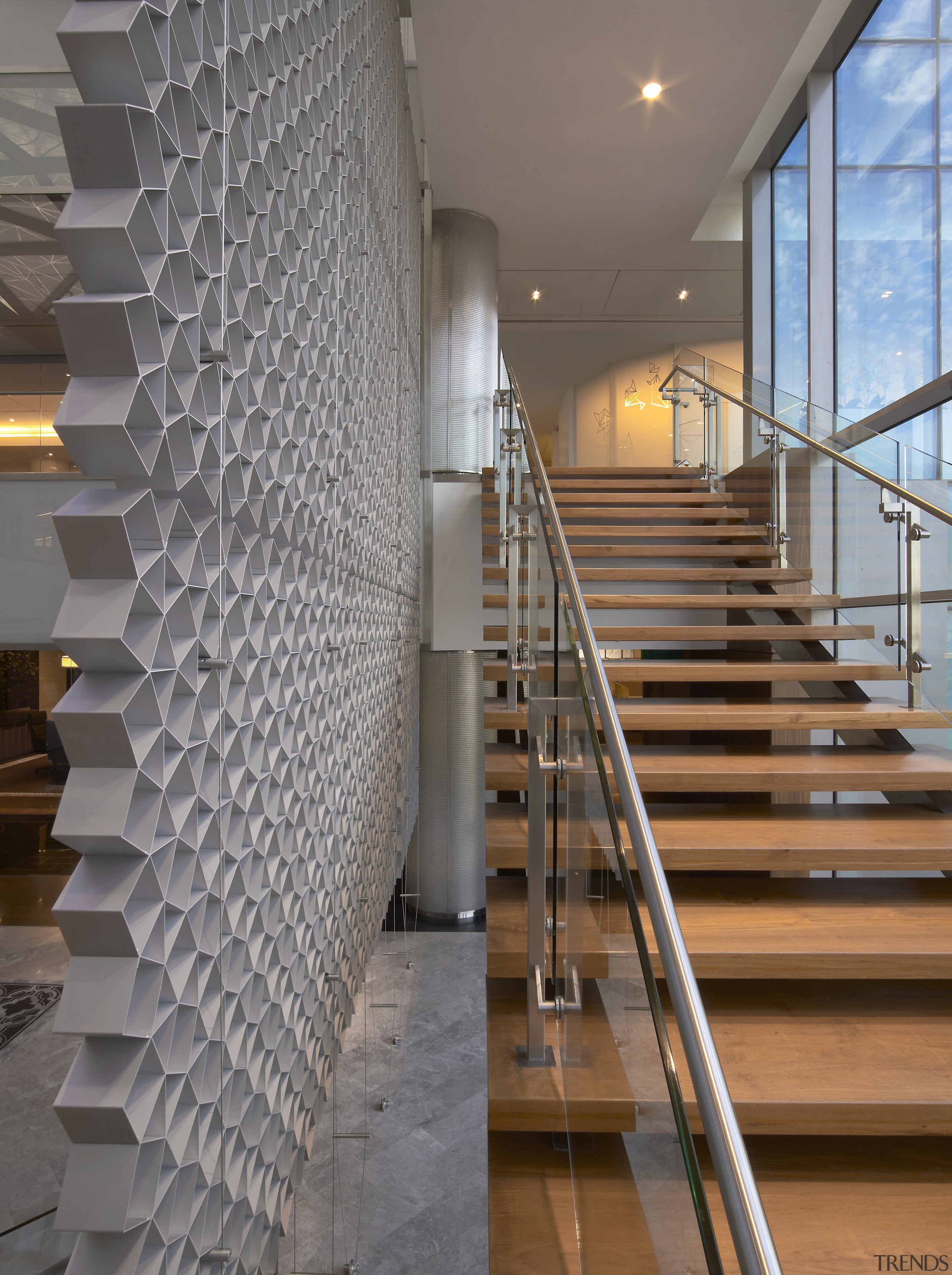 Wooden stairs with grey cutout feature wall. - architecture, baluster, building, daylighting, flooring, glass, handrail, interior design, lobby, stairs, structure, wall, gray