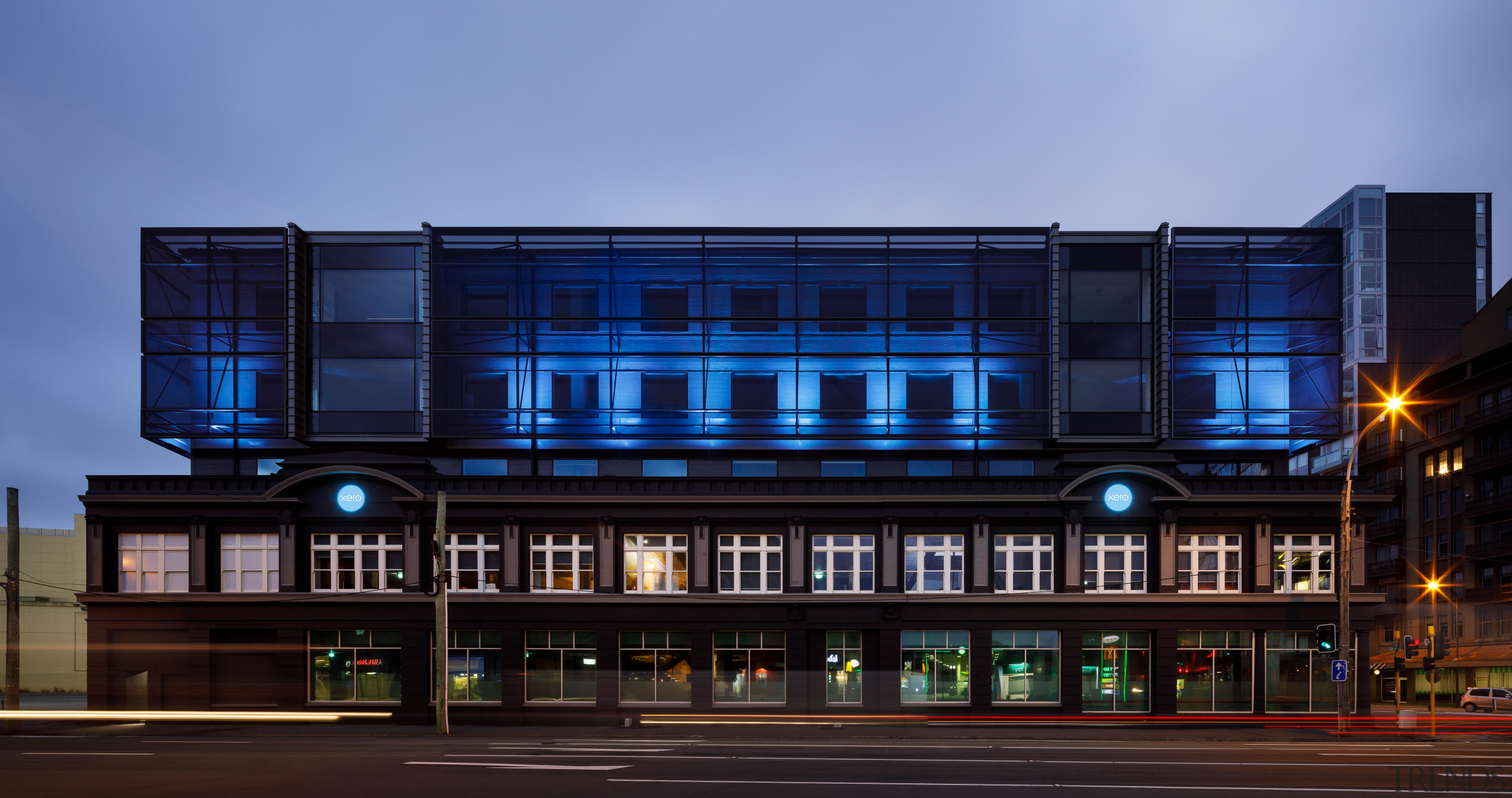 By night, the upper level facade of Xero's architecture, building, city, commercial building, corporate headquarters, evening, facade, headquarters, metropolitan area, mixed-use, night, sky, black, teal, blue